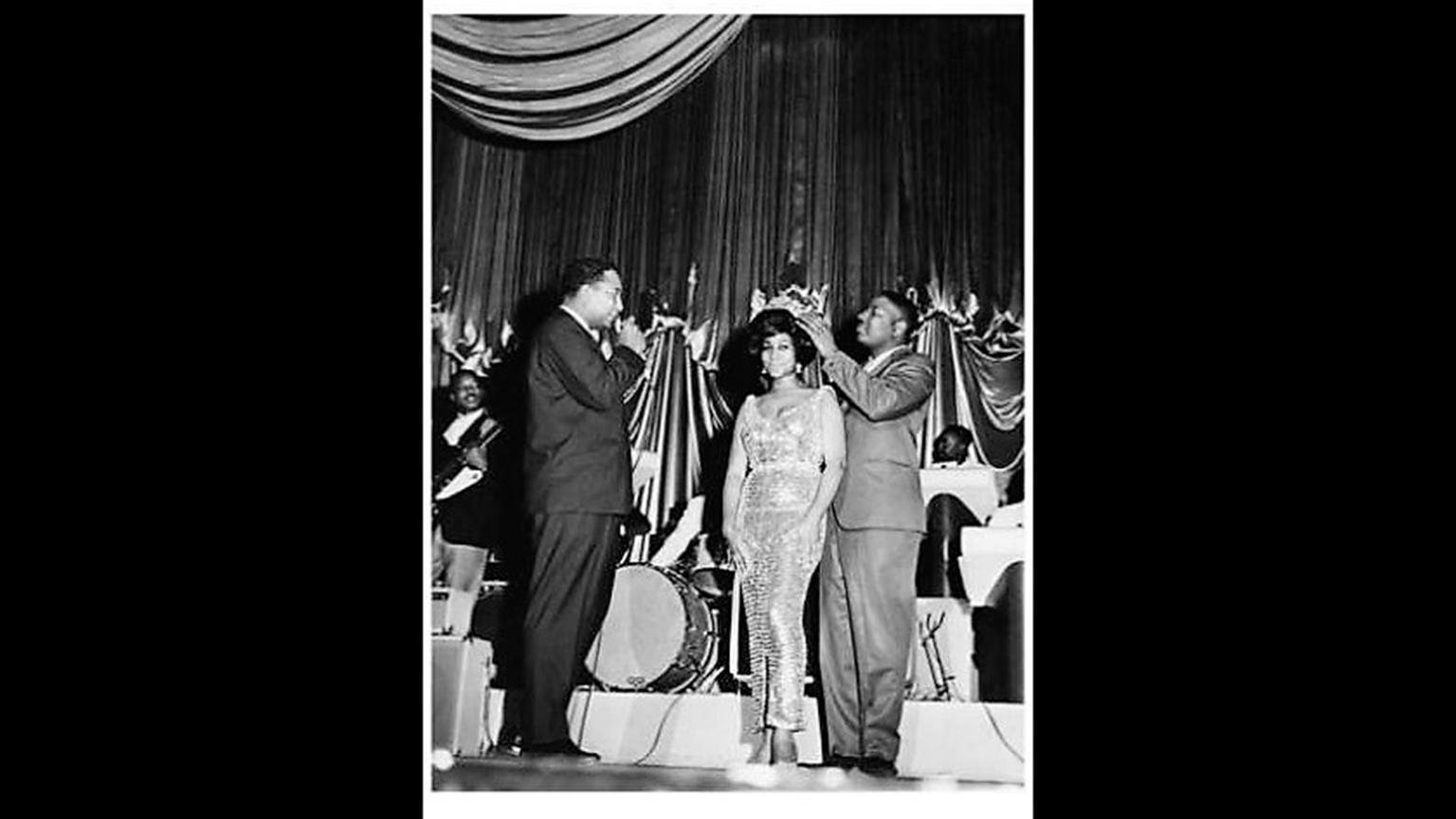 Aretha Franklin is crowned by Pervis Spann at the Regal Theater in May 1964 while Rodney Jones watches. (Courtesy of Jet Magazine)