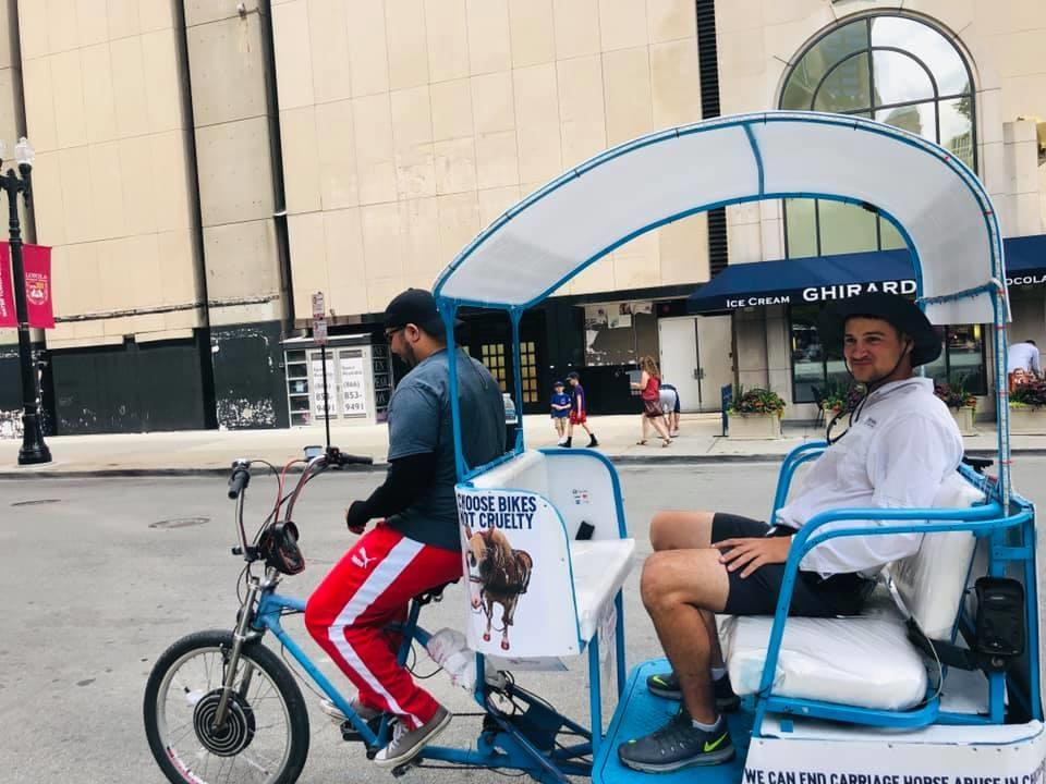 A Pedicab Ride Guys employee drives a passenger in a pedicab covered with advertisements from the Chicago Alliance for Animals. (Marla Rose / Facebook)