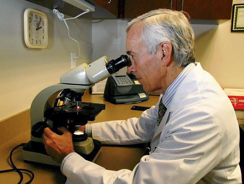 In this undated photo provided by Atlanta Allergy & Asthma, Dr. Stanley Fineman looks through a microscope at Atlanta Allergy & Asthma Center in Atlanta to examine pollen. (Robin B. Panethere / Atlanta Allergy & Asthma via AP)