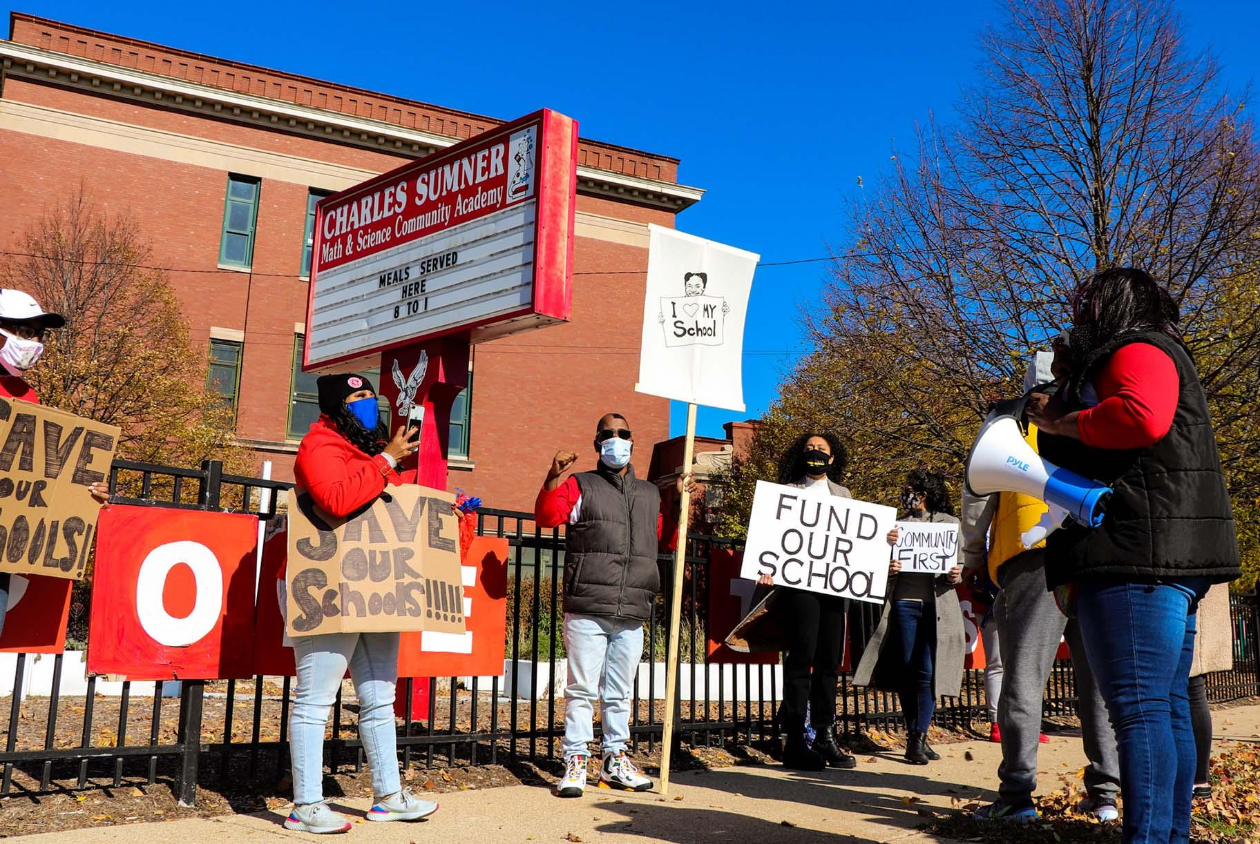 Protesters stand outside Charles Sumner Math and Science Community Academy on Saturday, Oct. 31, 2020. (Grace Del Vecchio / WTTW News)