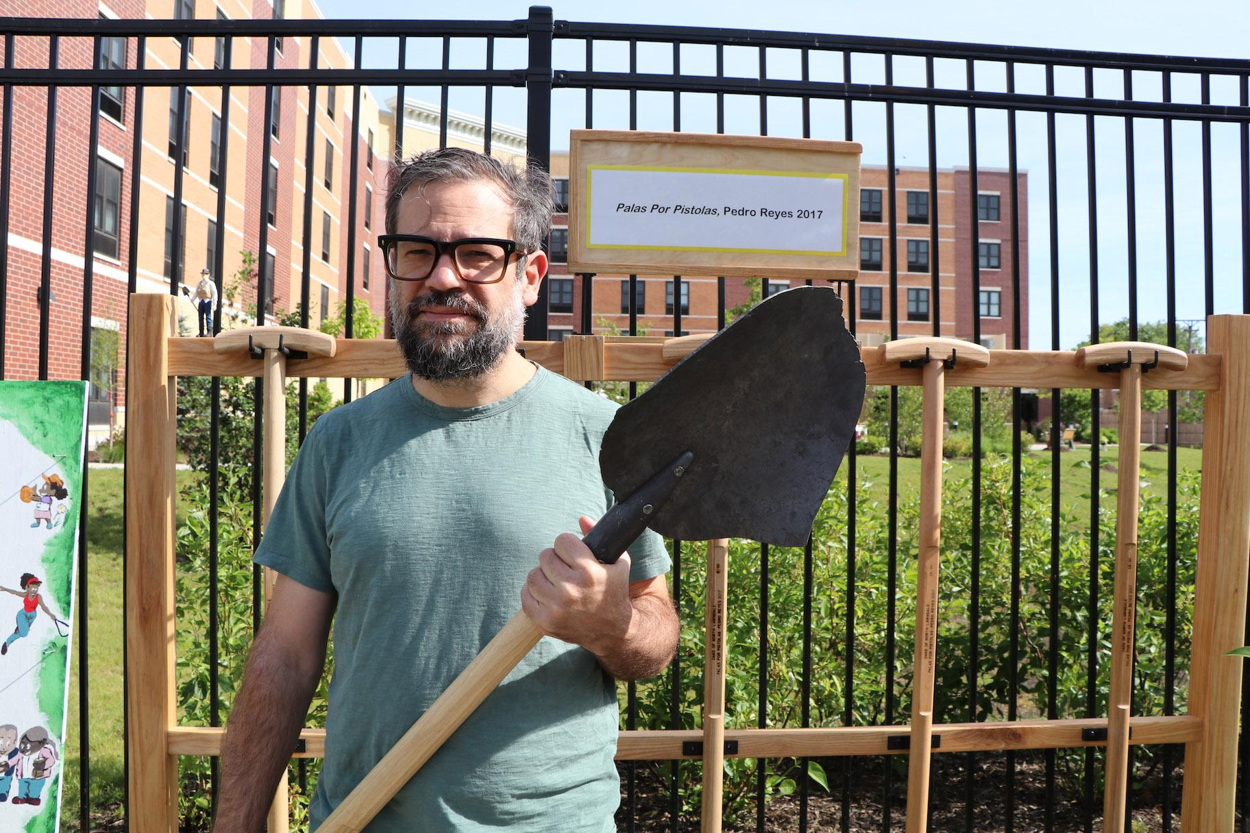 "Mexican artist Pedro Reyes holds a shovel that's part of his ""Palas por Pistolas"" collection. The shovel's head is made from melted guns. (Evan Garcia / WTTW)"