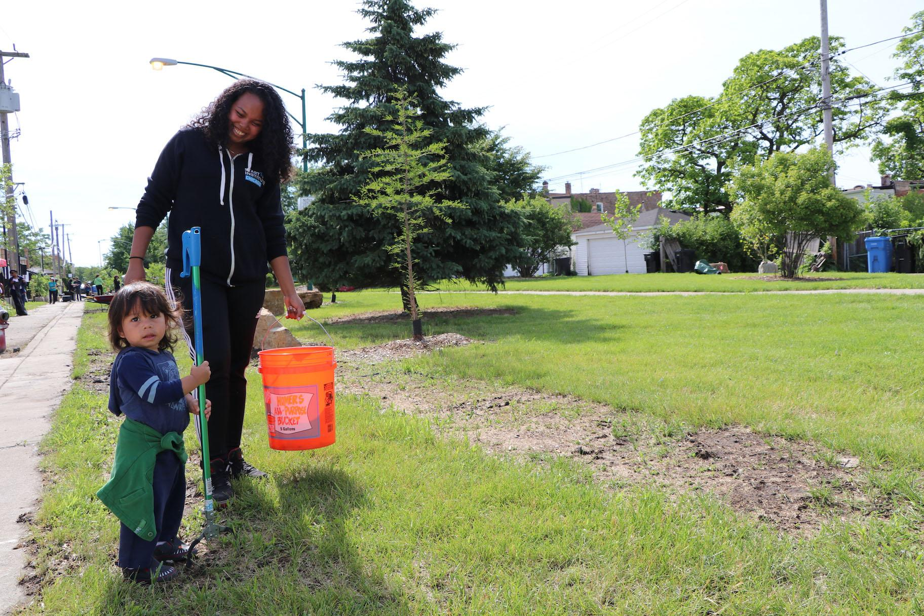 Volunteer Meia Santos and her son Arlo Garcia pick up litter at the event. (Evan Garcia / WTTW)