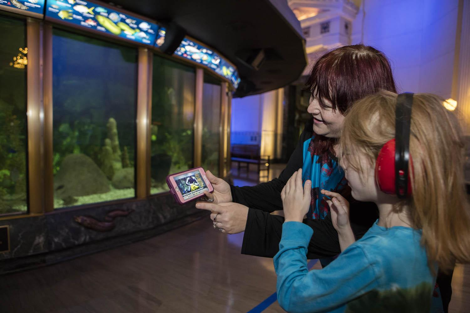 A mother and daughter explore Shedd's Sensory-Friendly App, designed for guests with autism or a sensory processing disorder, in front of the aquarium's Caribbean Reef exhibit. (Brenna Hernandez / Shedd Aquarium)