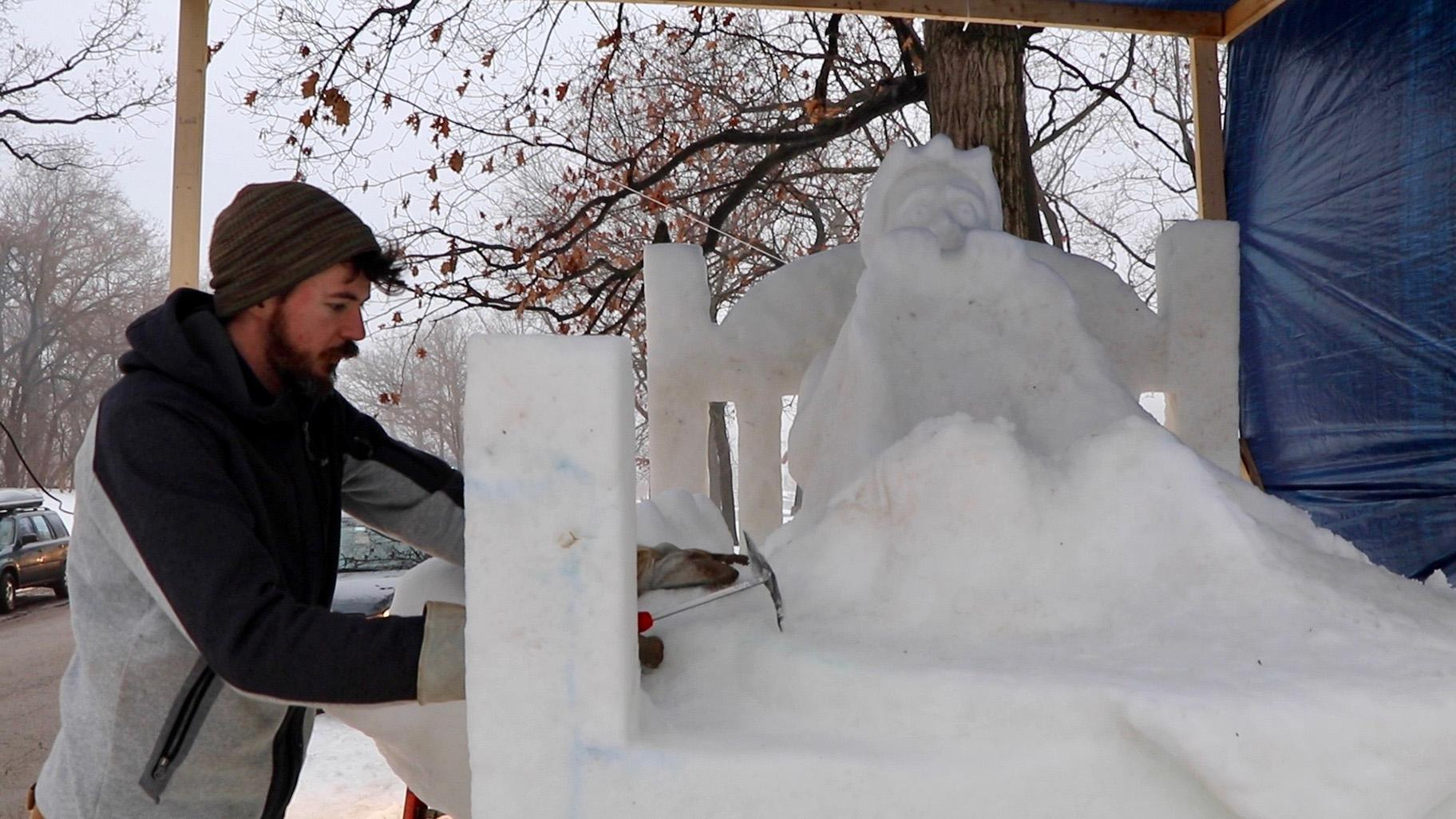 "Snow sculptor George Burnette works on his sculpture ""Don't Look Under the Bed"" on Friday during the Illinois Snow Sculpting Competition in Rockford, Illinois. (Evan Garcia / WTTW)"