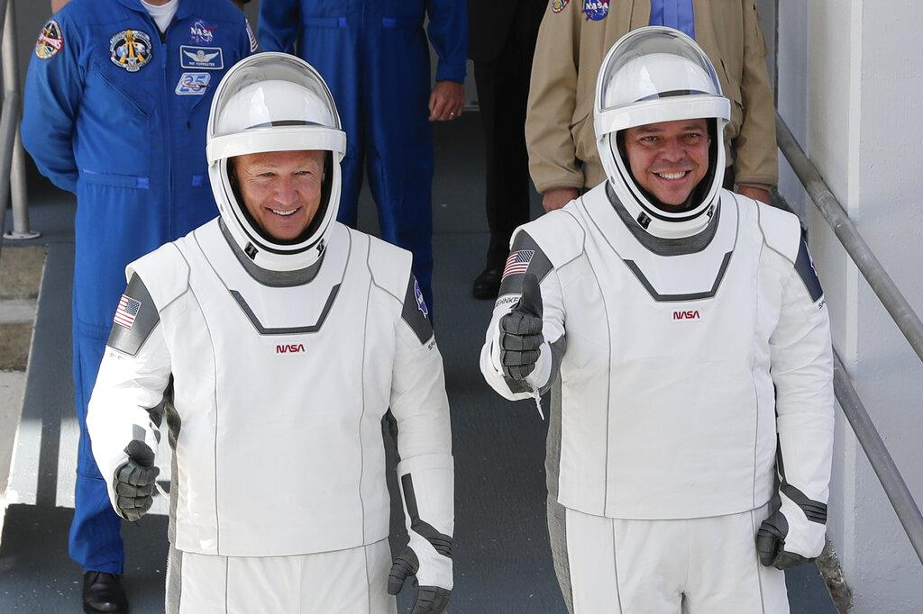 In this May, 30, 2020 file photo, NASA astronauts Douglas Hurley, left, and Robert Behnken walk out of the Neil A. Armstrong Operations and Checkout Building on their way to Pad 39-A, at the Kennedy Space Center in Cape Canaveral, Fla. (AP Photo / John Raoux, File)