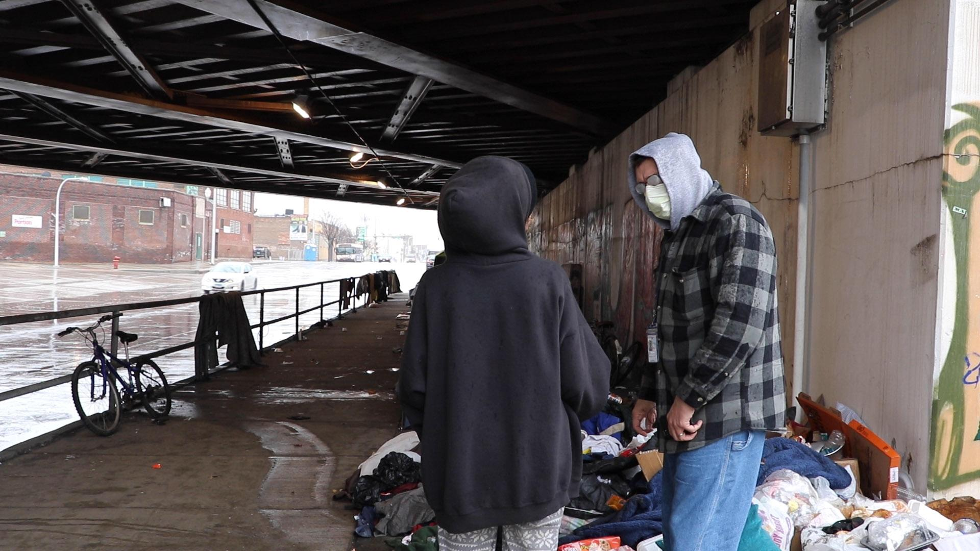 Stephan Koruba, a nurse practitioner with nonprofit The Night Ministry, speaks to a woman at a homeless encampment on Chicago's West Side. (Evan Garcia / WTTW News)