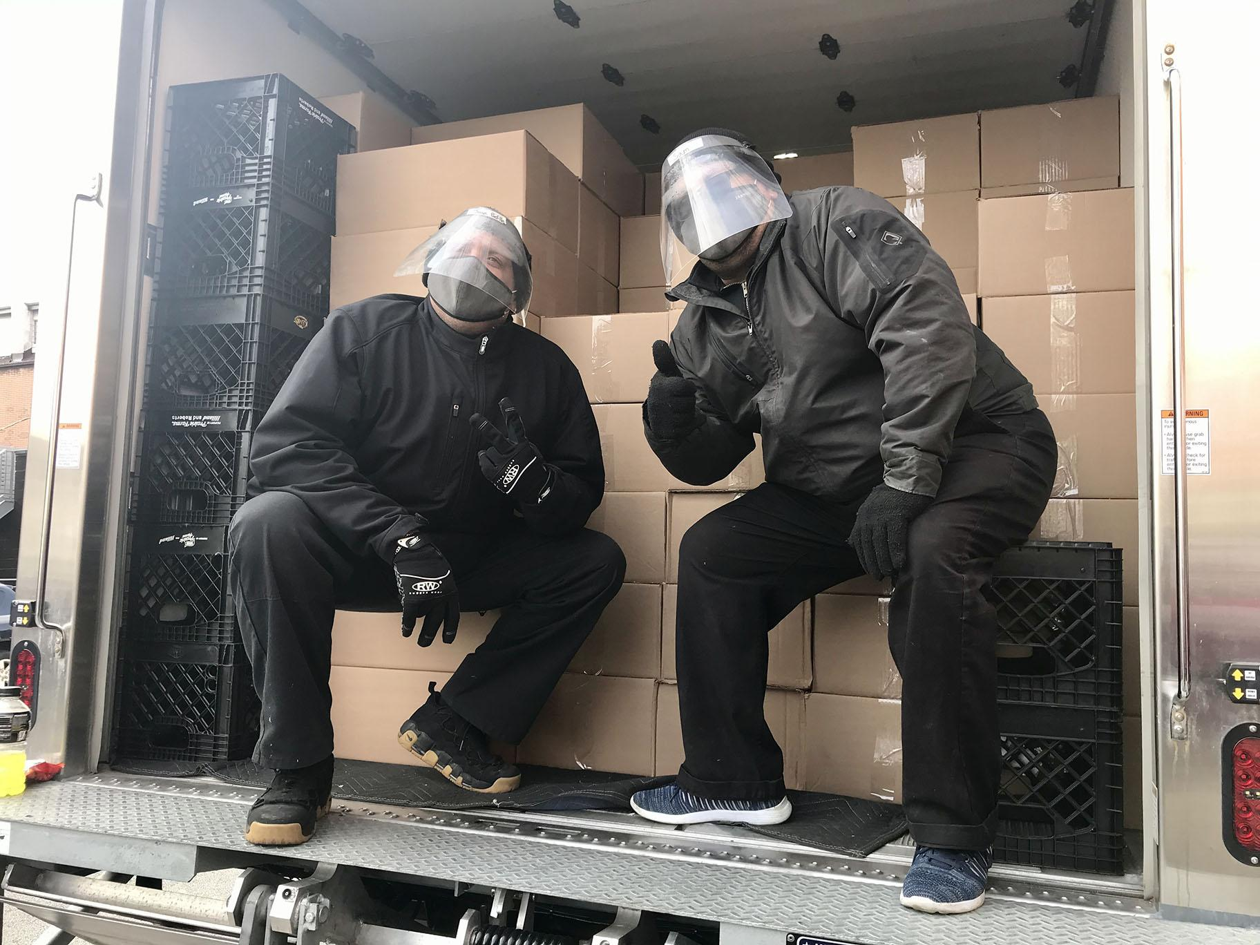 Catering by Michaels delivery truck drivers Sam Espada and Jose Padilla pose for a photo on Saturday, Nov. 21, 2020. (Ariel Parrella-Aureli / WTTW News)
