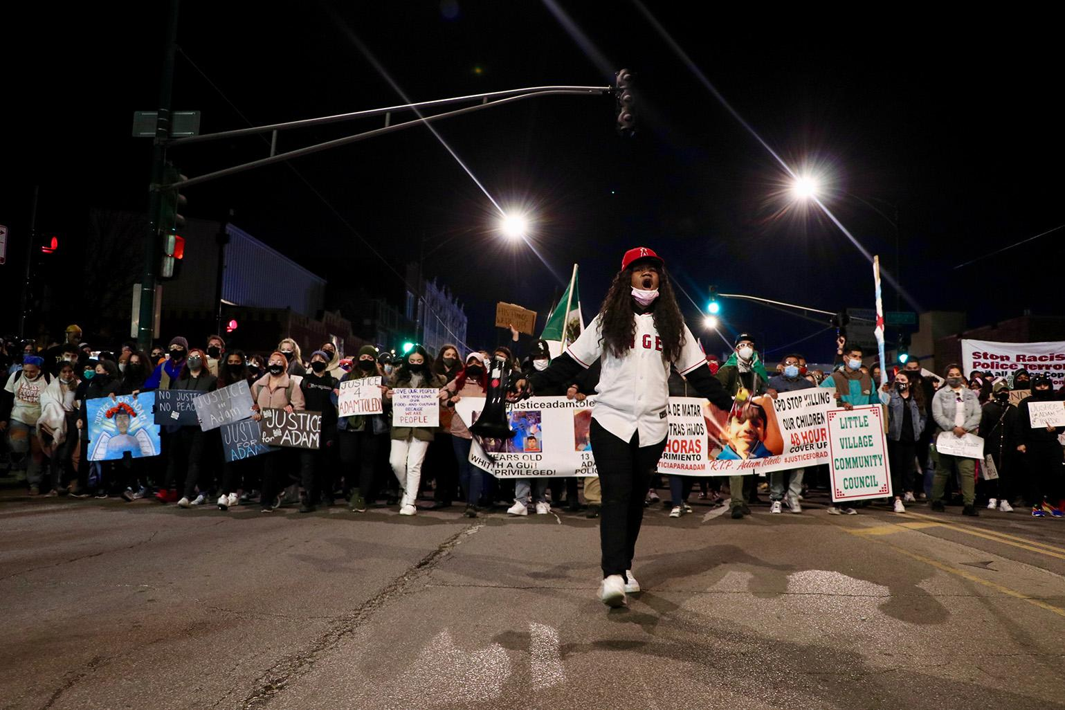 An organizer leads protesters along Fullerton Avenue April 16, 2021, during a protest over the fatal police shooting of 13-year-old Adam Toledo. (Evan Garcia / WTTW News)