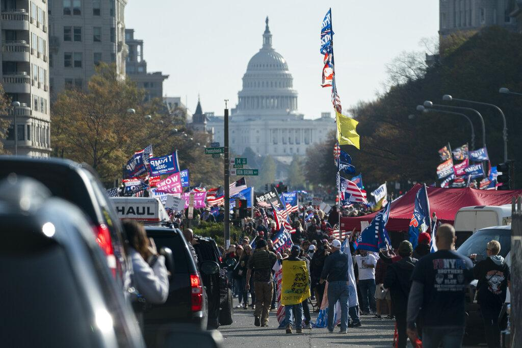 A motorcade carrying President Donald Trump drives by a group of supporters participating in a rally near the White House, Saturday, Nov. 14, 2020, in Washington. (AP Photo / Evan Vucci)