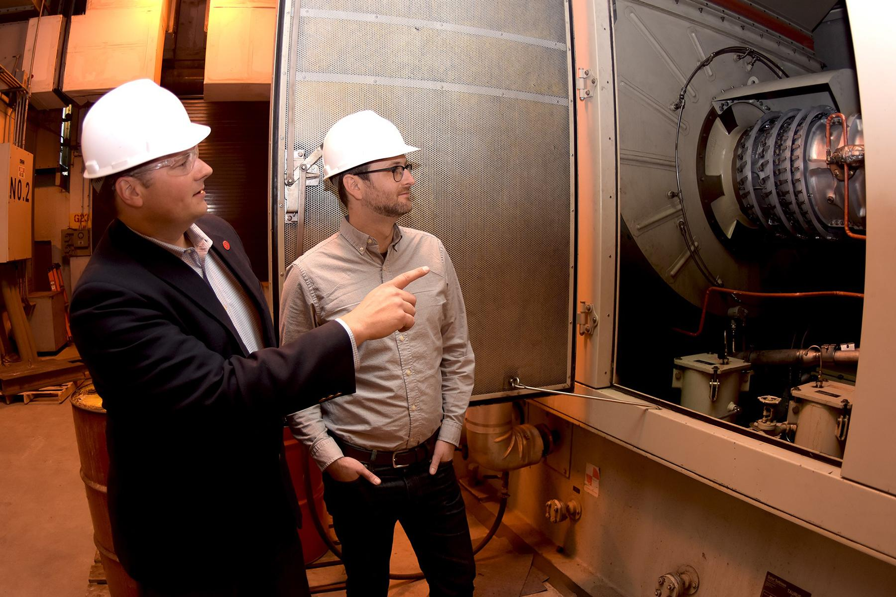 Cliff Haefke, director of the UIC Energy Resources Center, left, and policy analyst Graeme Miller analyze the 7-megawatt combined heat and power combustion turbine at the UIC West Campus Utilities Plant. (Courtesy University of Illinois at Chicago)