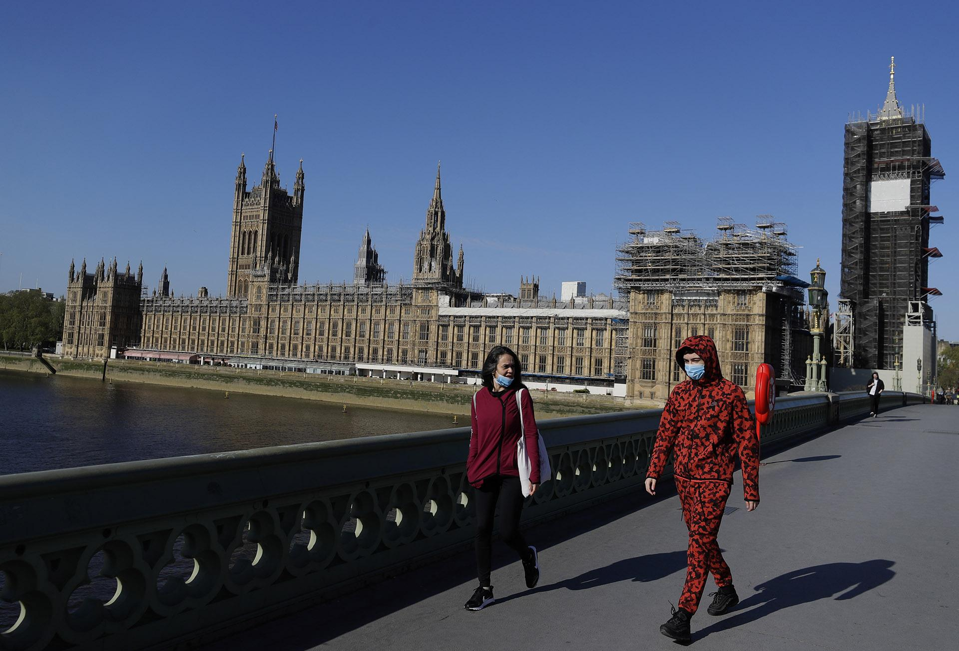 People wear masks as they walk near Britain's Houses of Parliament as the country is in lockdown to help curb the spread of coronavirus, in London, Tuesday, April 21, 2020. AP Photo / Kirsty Wigglesworth)