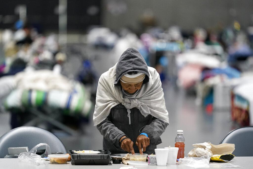 A woman eats at a homeless shelter inside the San Diego Convention Center Tuesday, Aug. 11, 2020, in San Diego. (AP Photo / Gregory Bull)