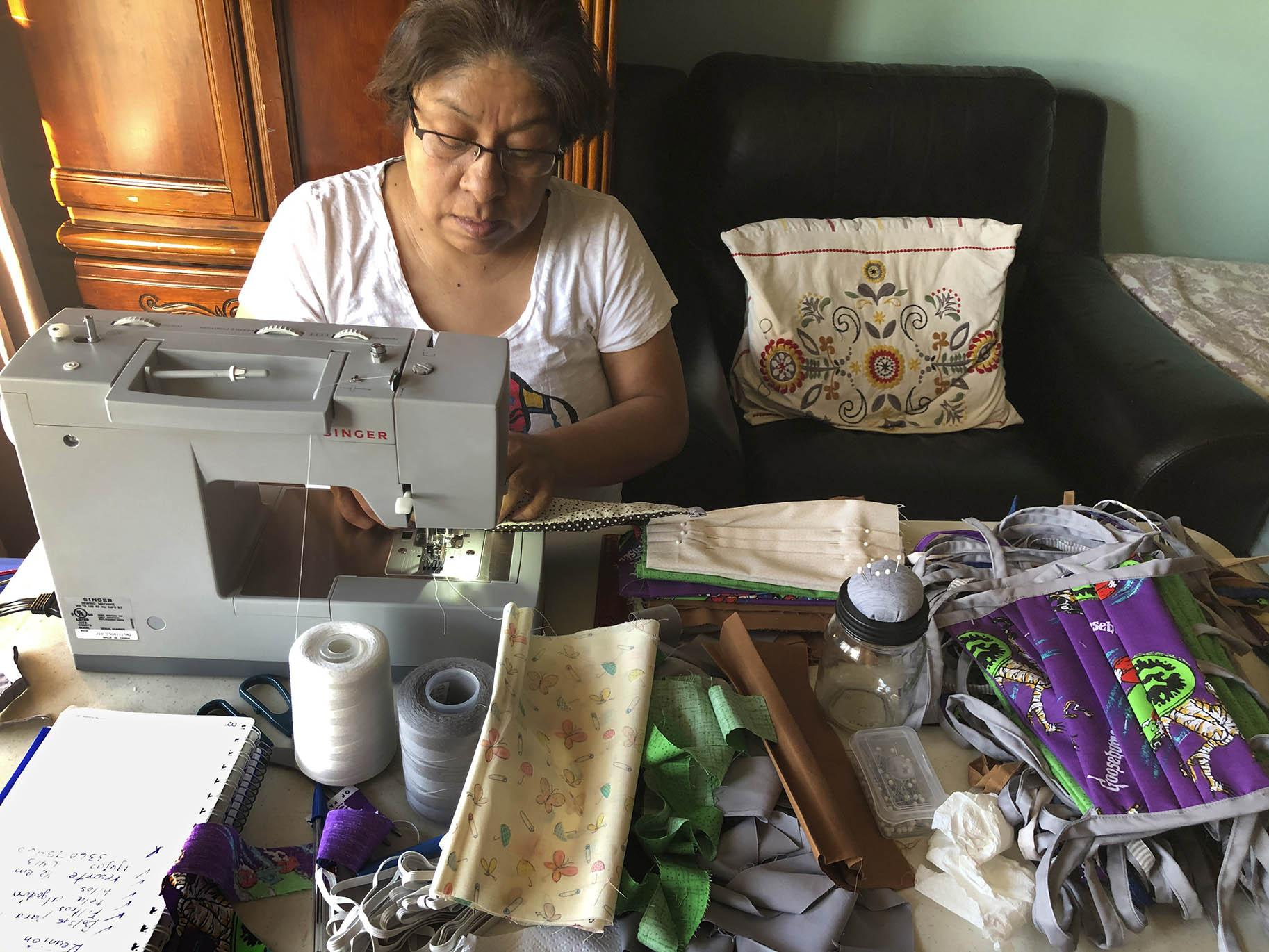 In this April 7, 2020, photo provided by Maribel Torres, Maribel Torres sews face masks masks to be used for protection against the coronavirus at her home in the Staten Island borough of New York. (Pablo Evangelista / Torres Family Photo via AP)