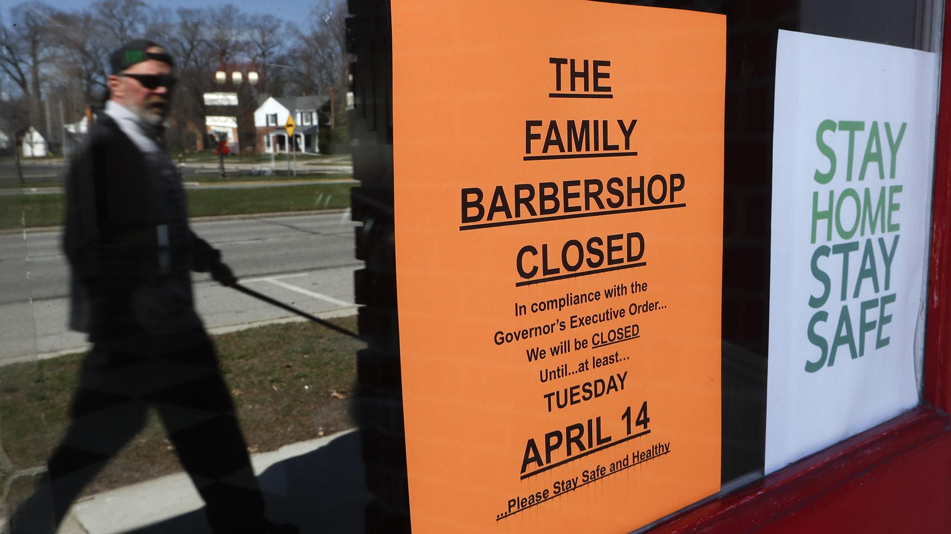 A pedestrian walks by The Family Barbershop, closed due to a Gov. Gretchen Whitmer executive order, in Grosse Pointe Woods, Mich., Thursday, April 2, 2020. (AP Photo / Paul Sancya)