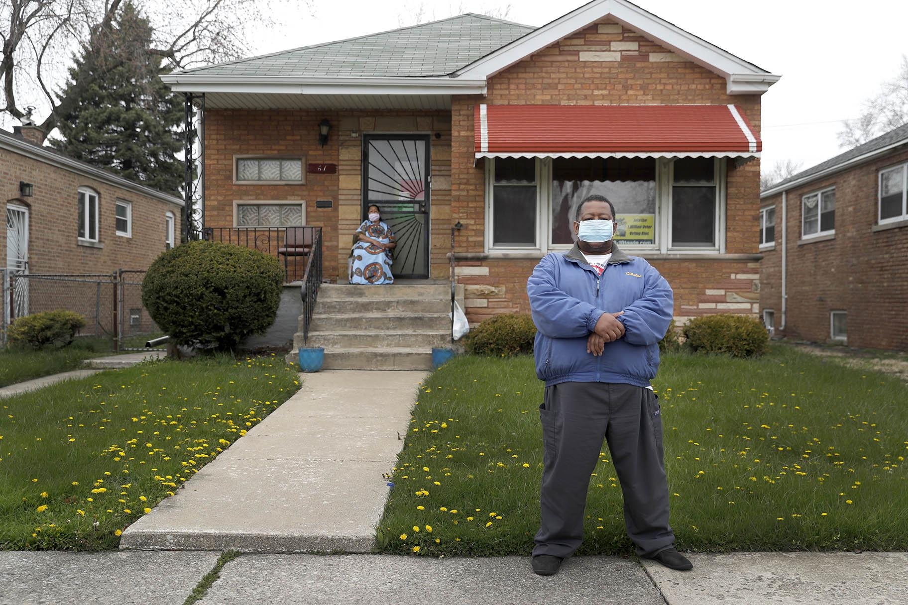 Anthony Travis, who has recovered from COVID-19 and lives with his sister, Jacqueline K. Johnson, background, and an adult daughter, poses for a portrait outside his Riverdale, Ill., home on Thursday, April 23, 2020. (AP Photo / Charles Rex Arbogast)