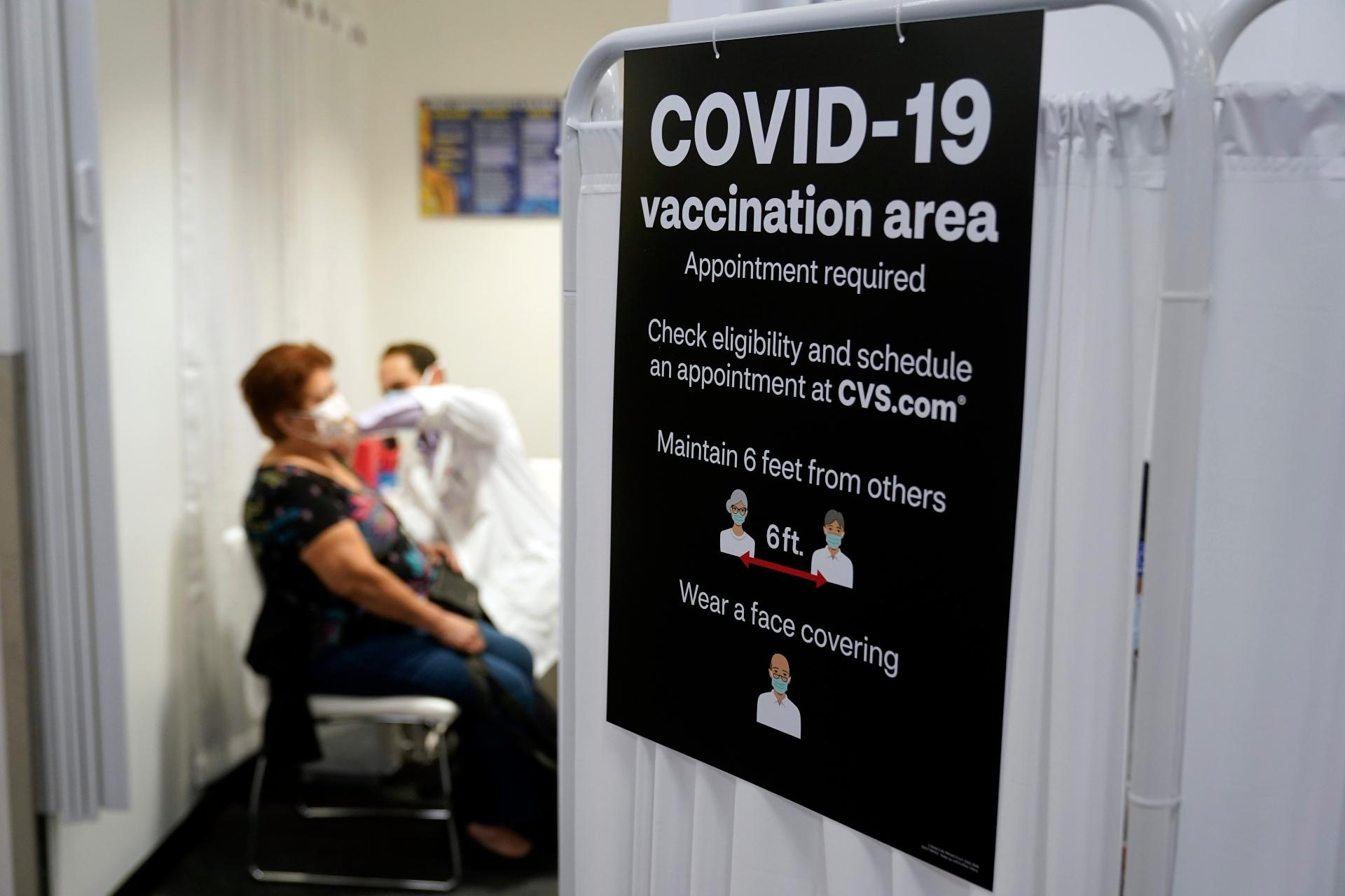 In this March 1, 2021, file photo, a patient receives a shot of the Moderna COVID-19 vaccine next to a guidelines sign at a CVS Pharmacy branch in Los Angeles. (AP Photo / Marcio Jose Sanchez, File)