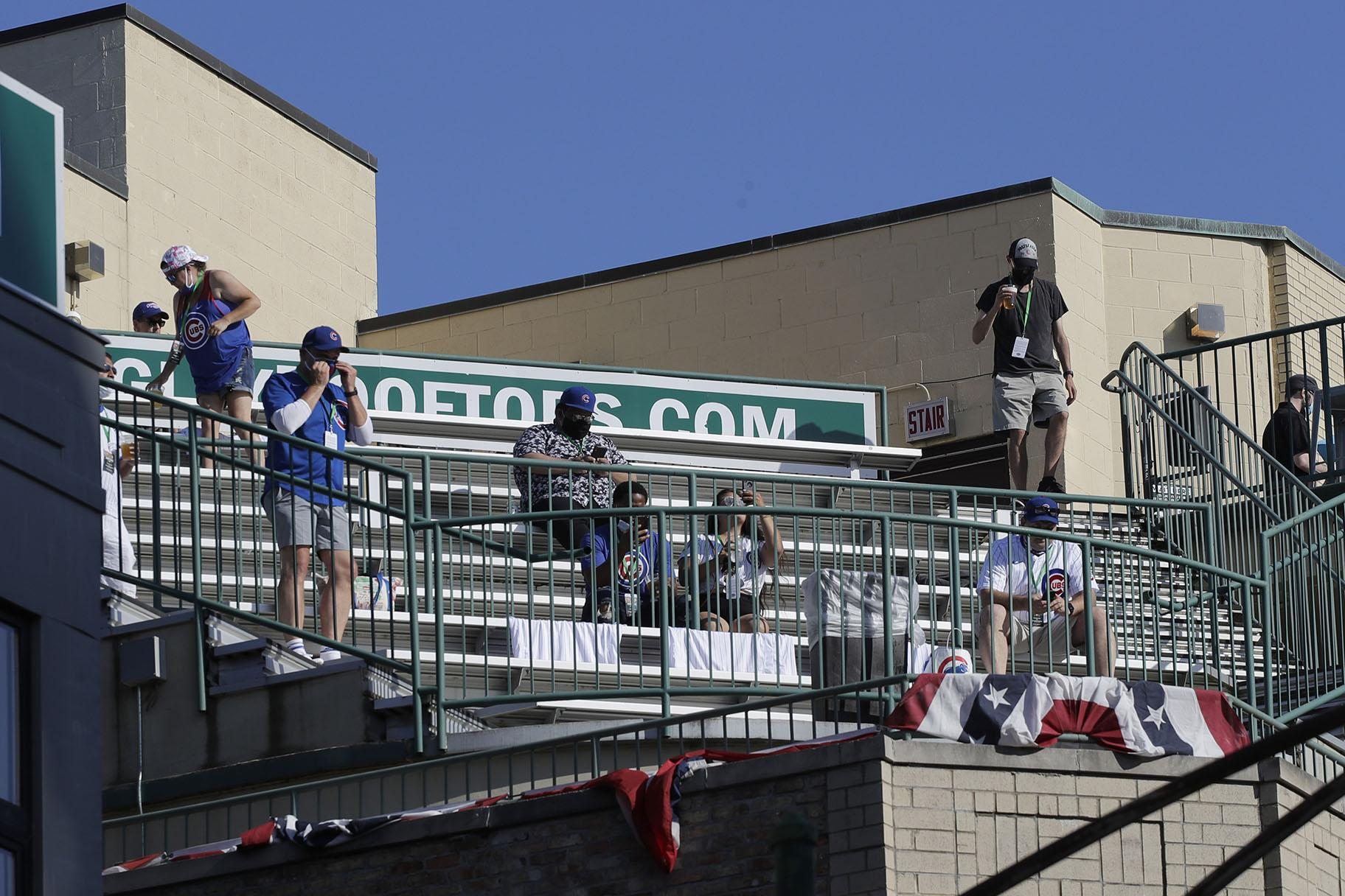 Chicago Cubs fans look to the field from a nearby rooftop before an opening day baseball game between the Chicago Cubs and the Milwaukee Brewers in Chicago, Friday, July 24, 2020, in Chicago. (AP Photo / Nam Y. Huh)
