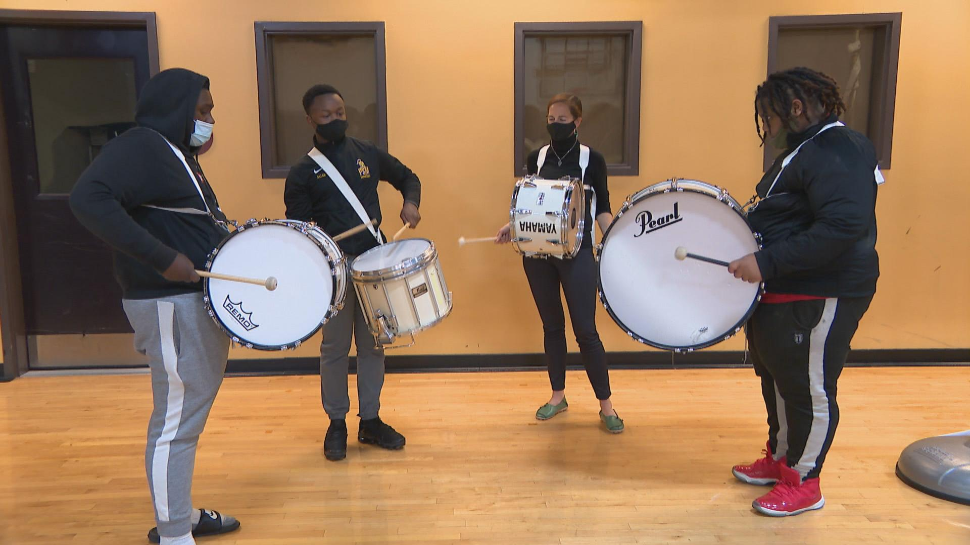 The drum line of BandWith rehearses inside the gymnasium of Marillac St. Vincent Family Services in East Garfield Park on Oct. 15, 2020. Snare drummer Marquis Allen, second to left, is the student instructor of the drum ensemble. (WTTW News)