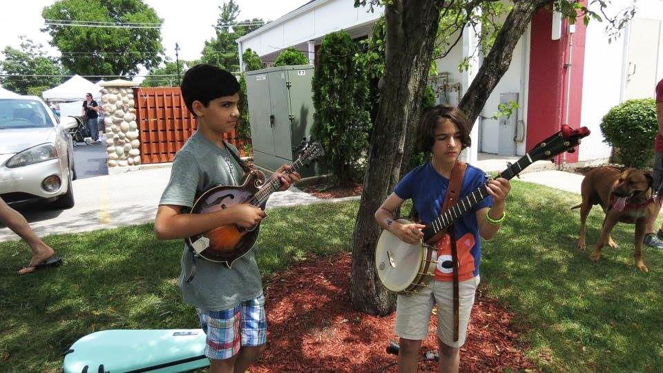 Kids try their thumbs at the art of the strum. (Frankfort Bluegrass Festival / Facebook)