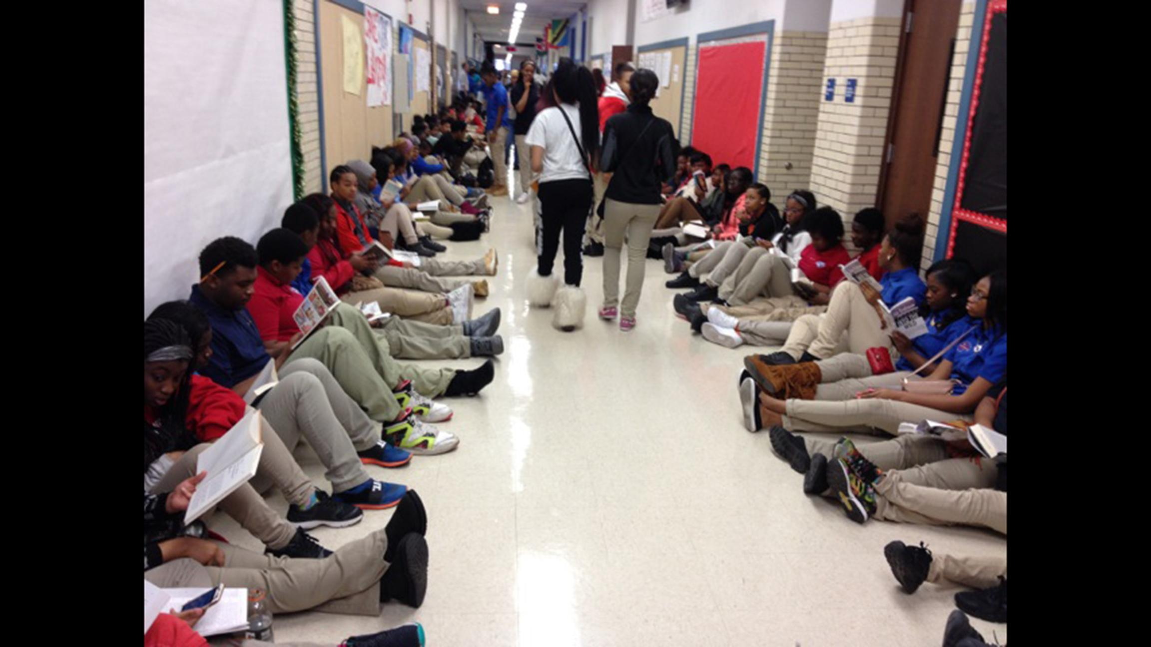 Students throughout the DuSable campus sat outside their classrooms reading last December to protest the firing of librarian Sara Sayigh. She was re-hired by the district, but had her position cut to half-time during the latest round of CPS staff cuts. (Courtesy of Alvita Payne)