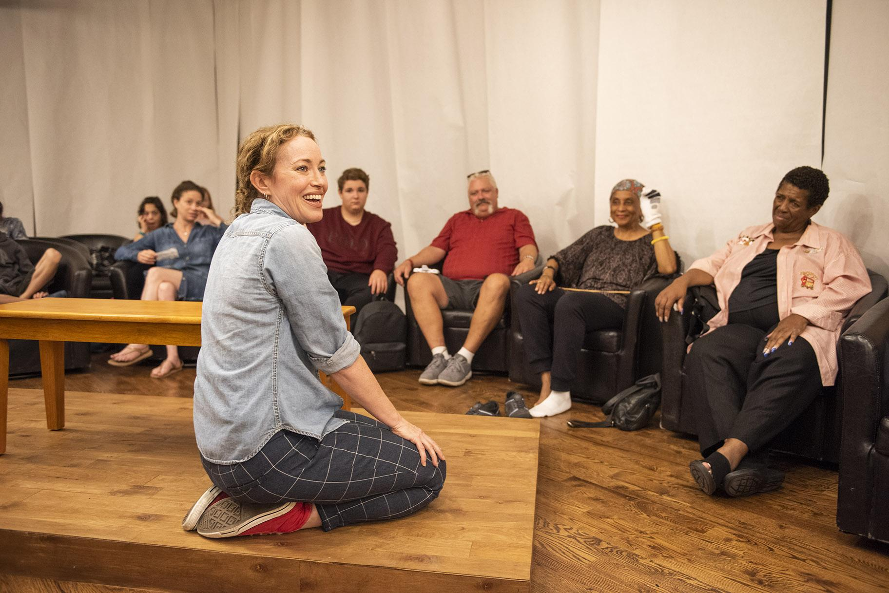 "Rebecca Spence sits on a tabletop with audience members in ""Every Brilliant Thing."" (Photo credit: Michael Brosilow)"