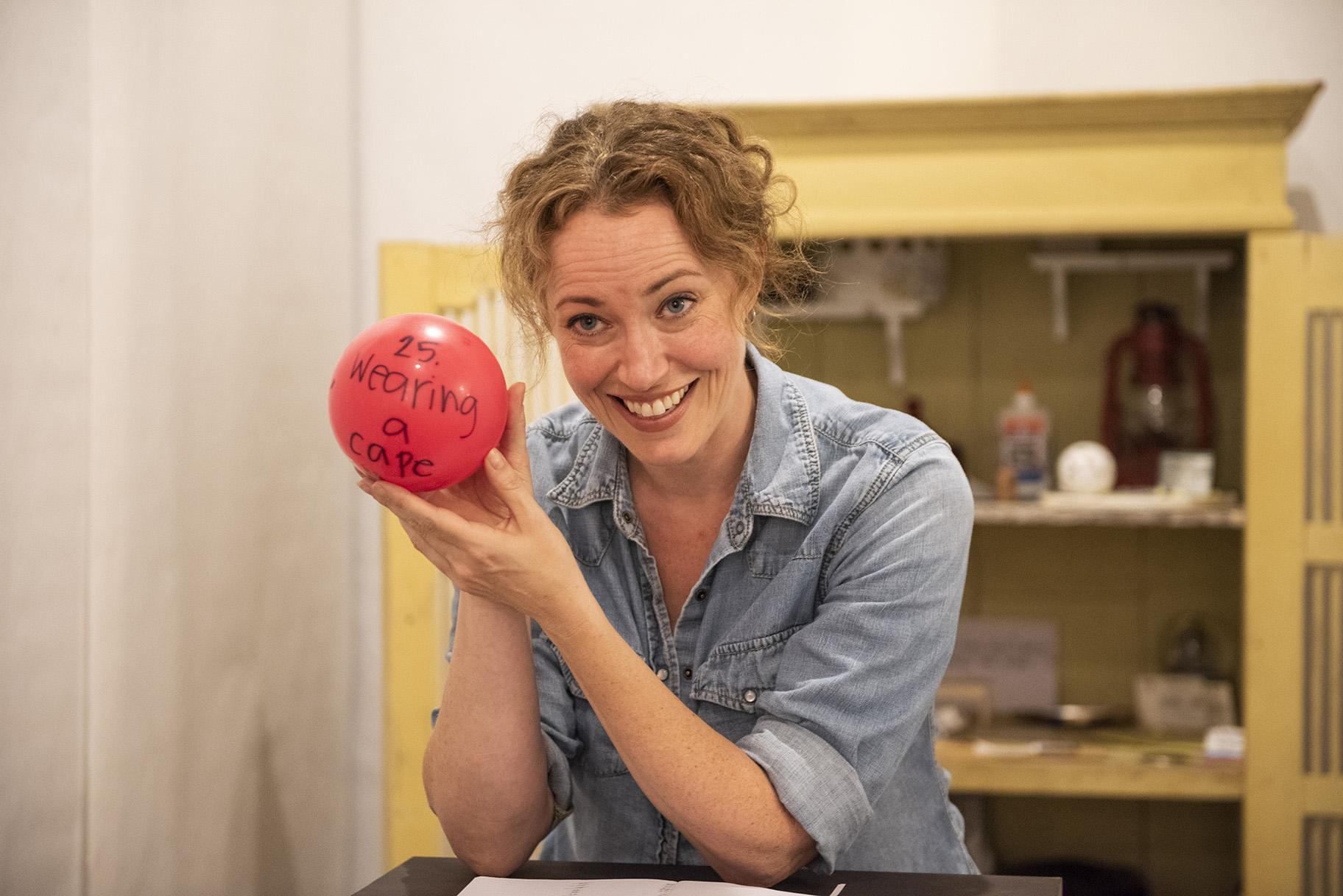 "Rebecca Spence holds up a red balloon in ""Every Brilliant Thing."" (Photo credit: Michael Brosilow)"