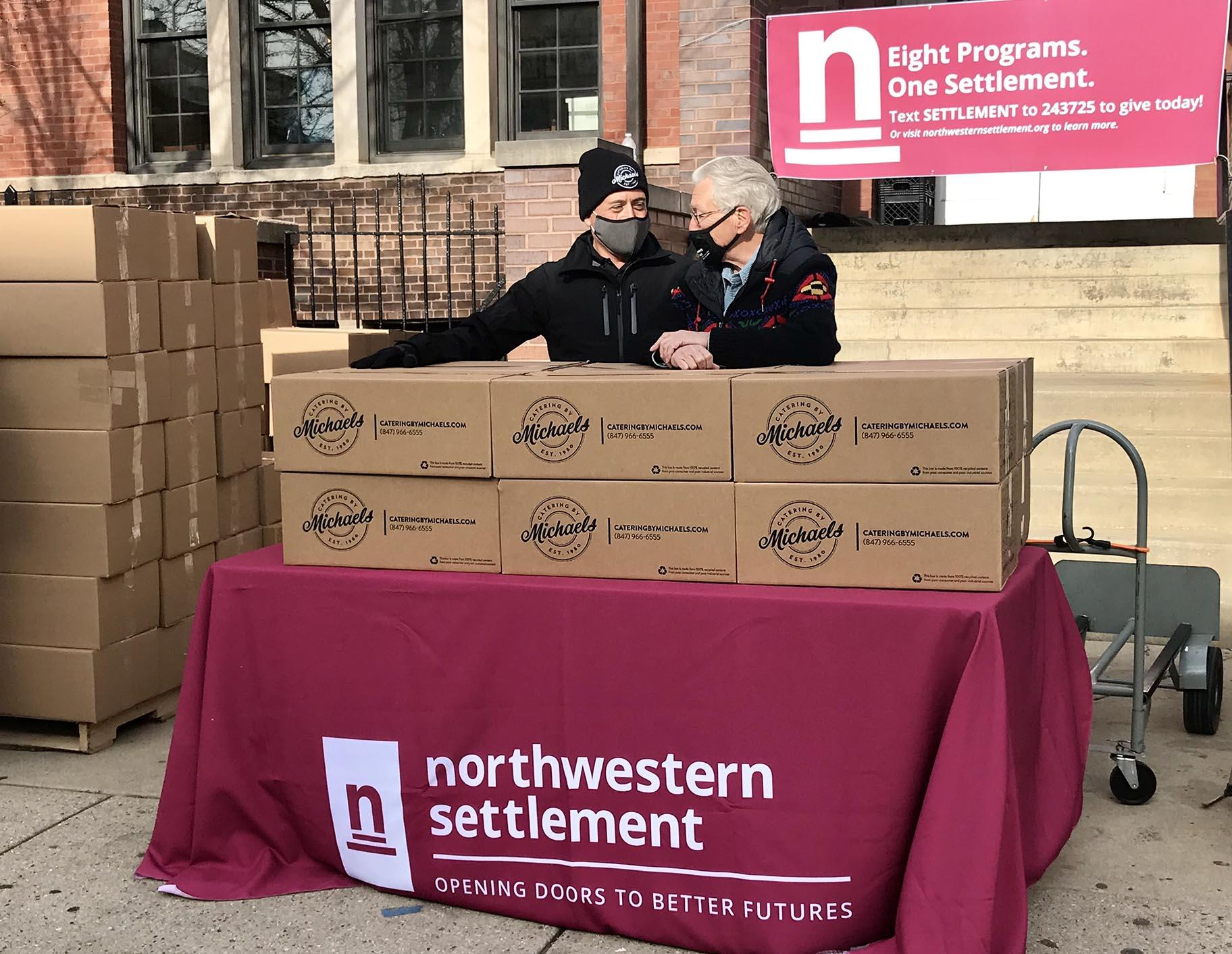 Stewart Glass, left, president of Catering by Michaels, and Ron Manderschied, president of Northwestern Settlement, stand with some of the Thanksgiving boxes before handing them out to the community. (Ariel Parrella-Aureli / WTTW News)