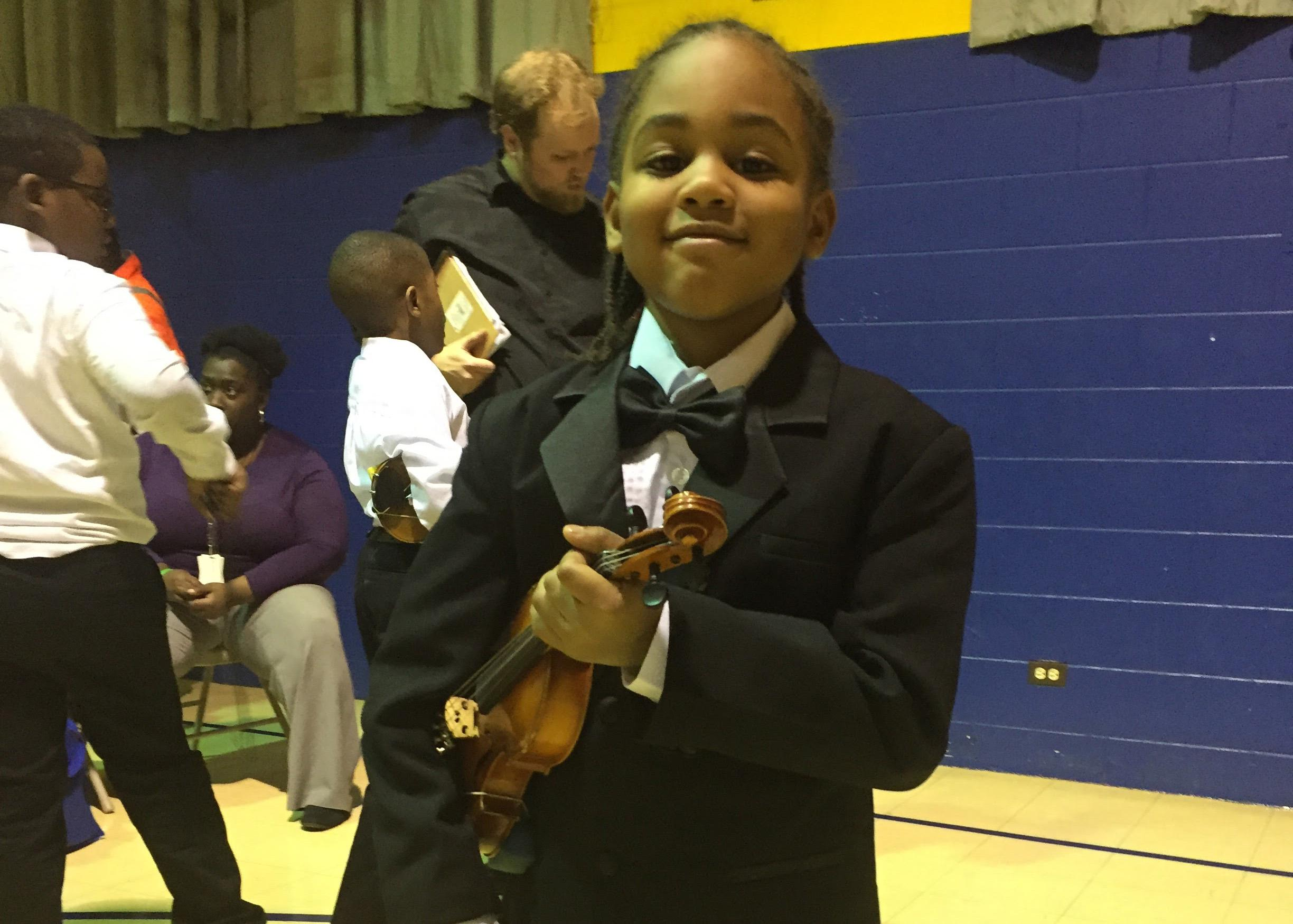 A student clutches his violin at a M.U.S.I.C. Inc performance. (Courtesy of Sarah Dupuis)