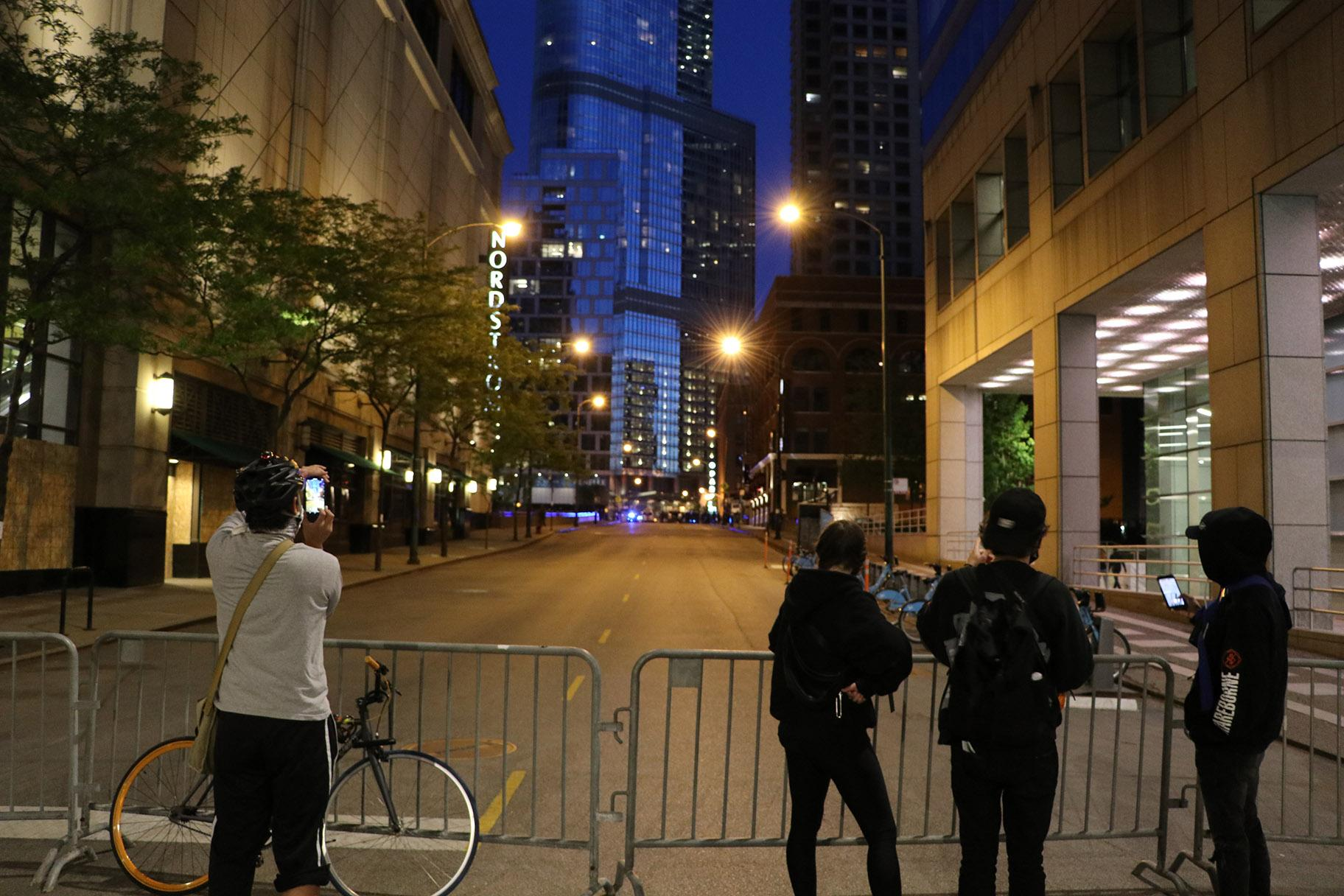 Onlookers photograph the police presence on Wabash Avenue behind a barricade. (Evan Garcia / WTTW News)