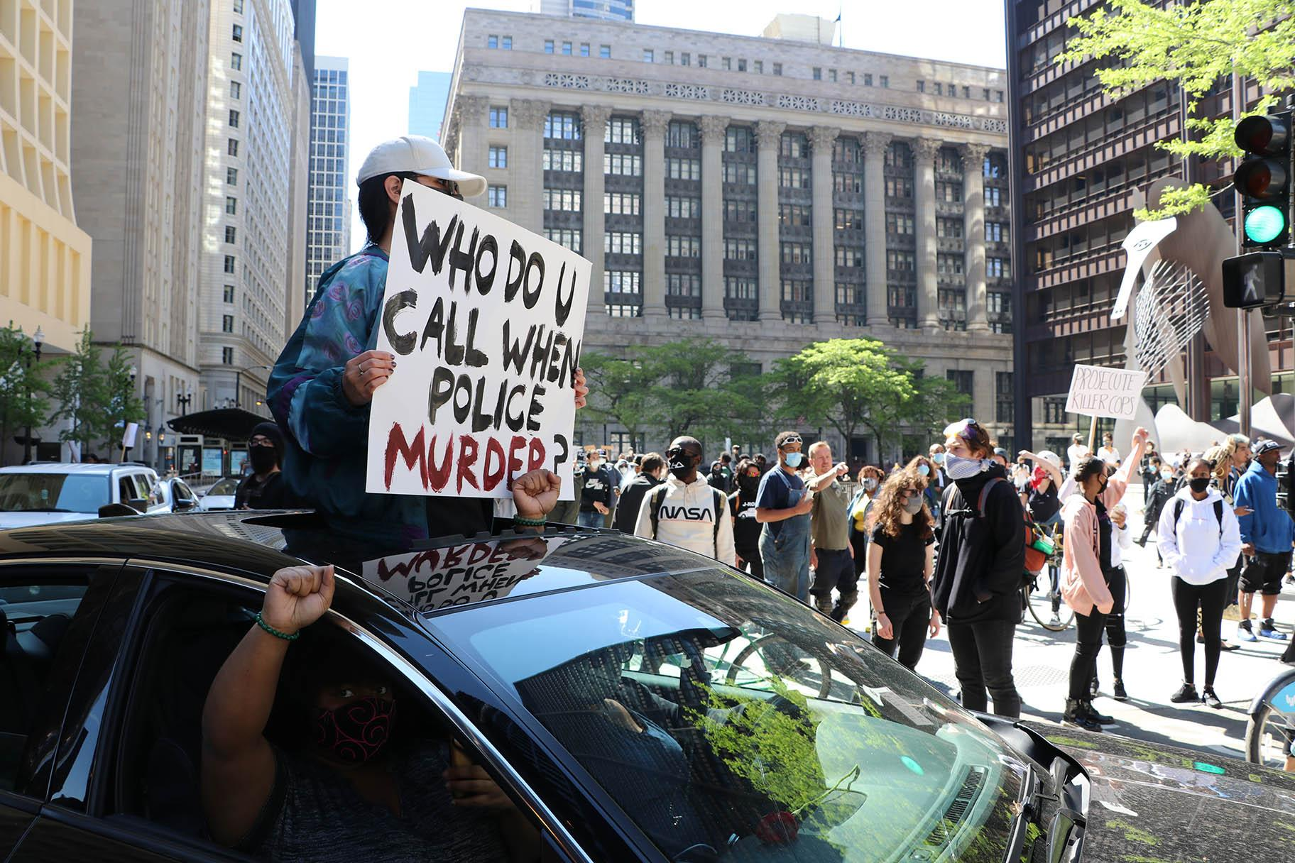 Several motorists show support by honking their horns and holding signs while circling Daley Plaza. (Evan Garcia / WTTW News)