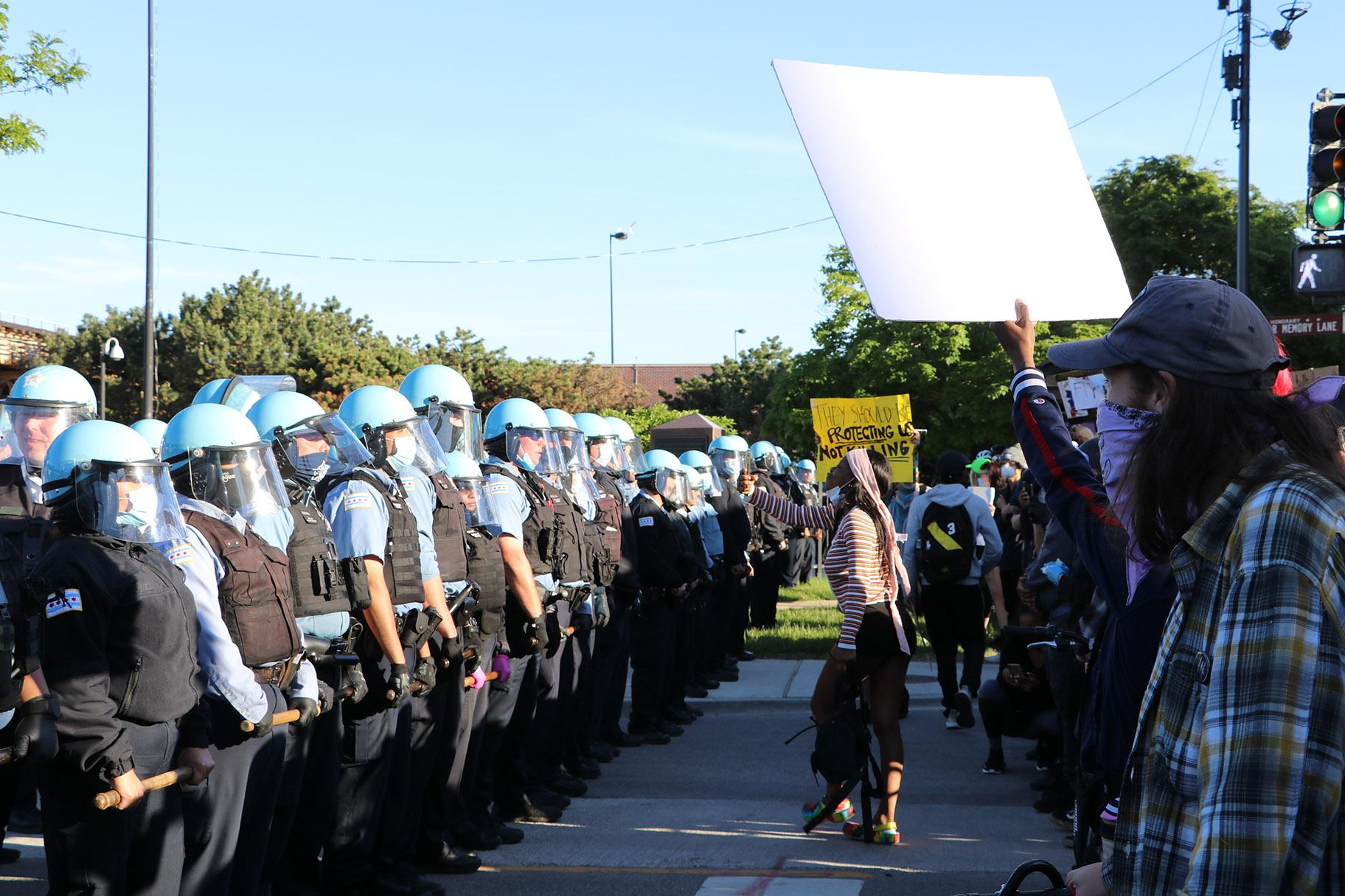 Protesters yell at a line of police officers at State and 35th streets, about 3 miles south of the Loop, where police set up a blockade. (Evan Garcia / WTTW News)