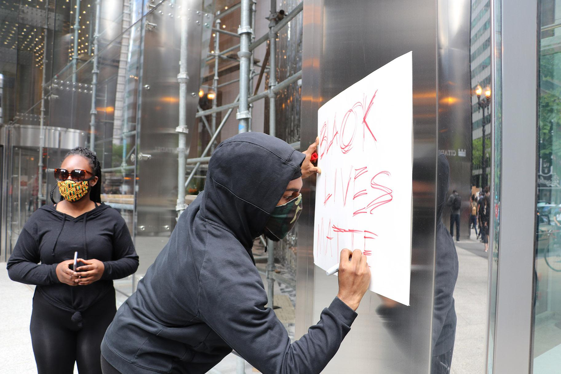 "Khalladi Taylor, 23, of Edgewater, draws a Black Lives Matter sign during the protest. ""I'm a black man and it affects me every time I see things like George Floyd,"" Taylor said. ""And it's not just George Floyd, it's a bunch of cases across not just this month or this year, that affect me personally. And I feel like it happens here in this city as well, so that's why I need to be out here with my people."" (Evan Garcia / WTTW News)"