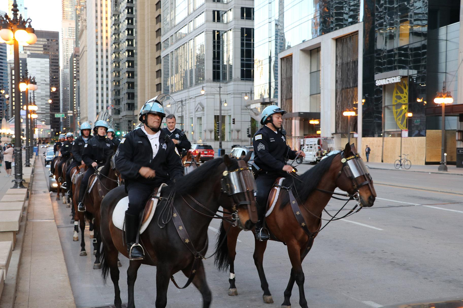 Police officers on horseback line up near the LaSalle Street bridge, the only visibly lowered bridge in the area. (Evan Garcia / WTTW News)