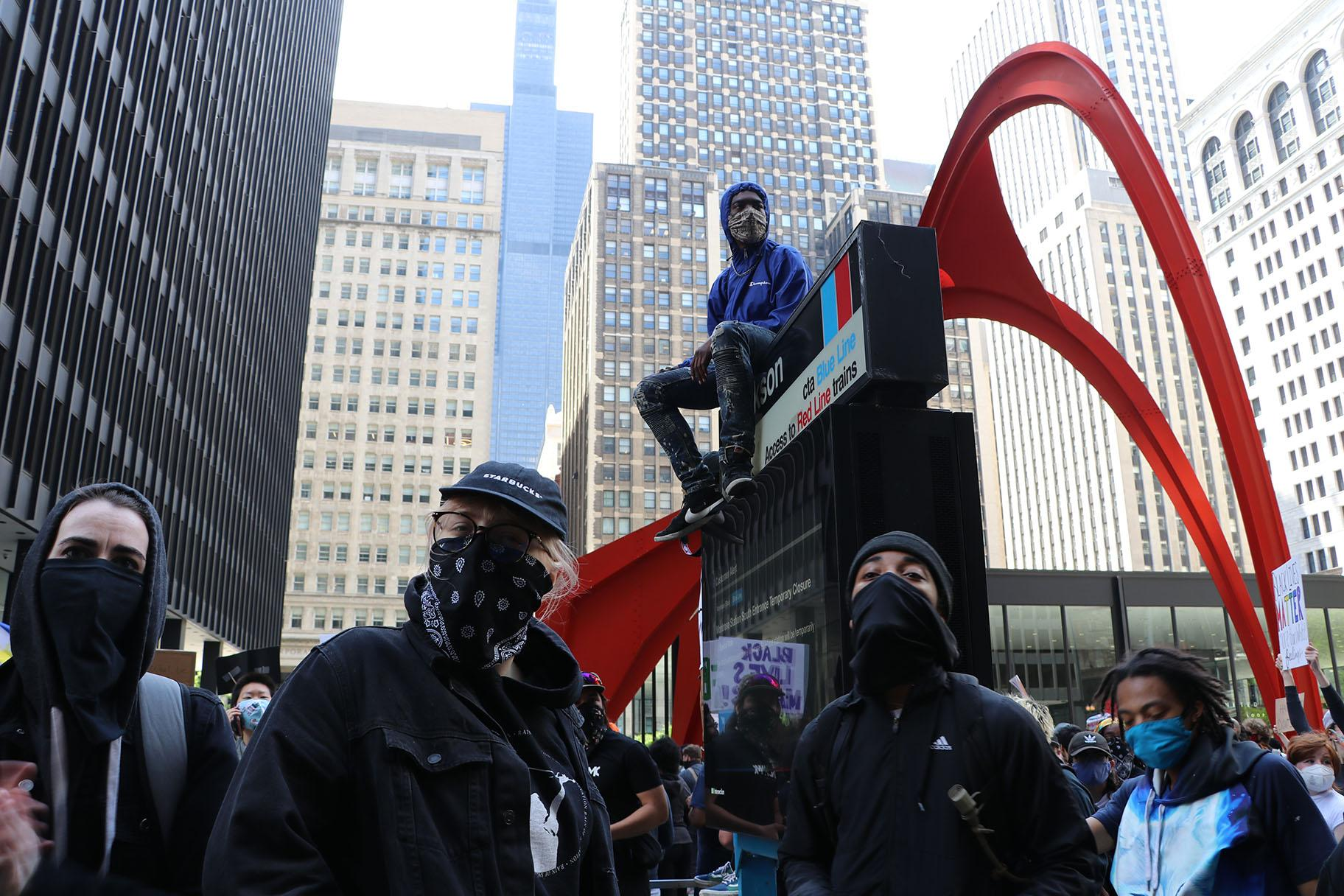 A protester sits on a CTA sign in front of Federal Plaza. (Evan Garcia / WTTW News)