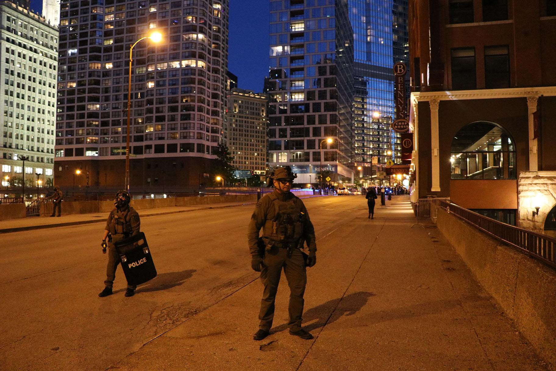Two members of Chicago Police's SWAT team block people from traveling northward on Wabash Avenue after the 9 p.m. curfew. Exceptions were made for people who live in the area. (Evan Garcia / WTTW News)
