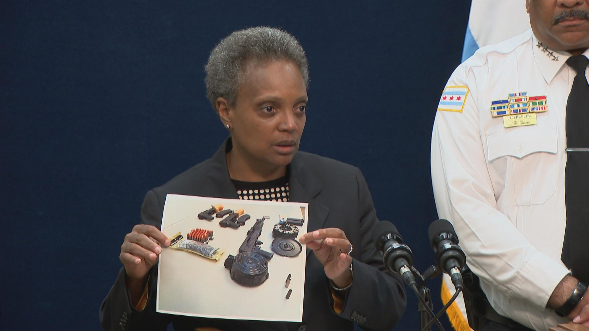 "At a press conference Tuesday, Aug. 6, Mayor Lori Lightfoot holds a photograph of evidence seized from two suspects, including armor-piercing bullets and a gun with a customized ""drum magazine that can hold 200-plus bullets."" (WTTW News)"