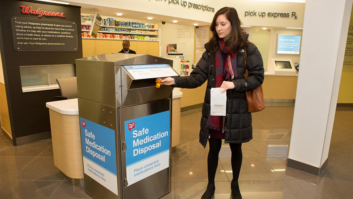 A woman discards medicine at a Walgreens medication disposal kiosk. (Walgreens)