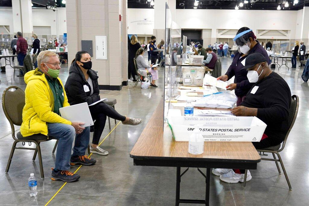 Election workers, right, verify ballots as recount observers, left, watch during a Milwaukee hand recount of presidential votes at the Wisconsin Center, Friday, Nov. 20, 2020, in Milwaukee. (AP Photo / Nam Y. Huh)