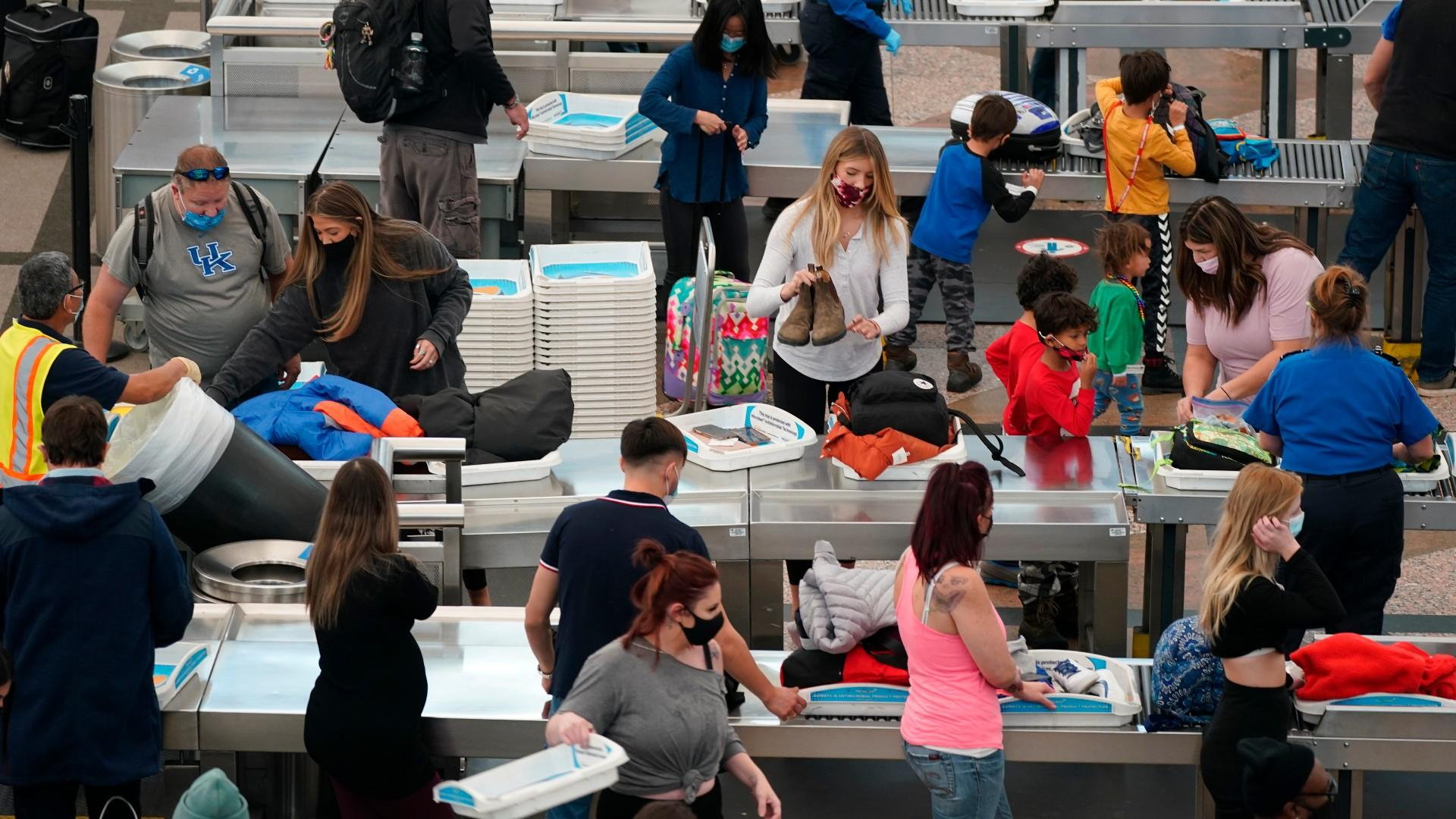 Travelers wear face masks while passing through the south security checkpoint in the main terminal of Denver International Airport Tuesday, Dec. 22, 2020, in Denver. (AP Photo / David Zalubowski)