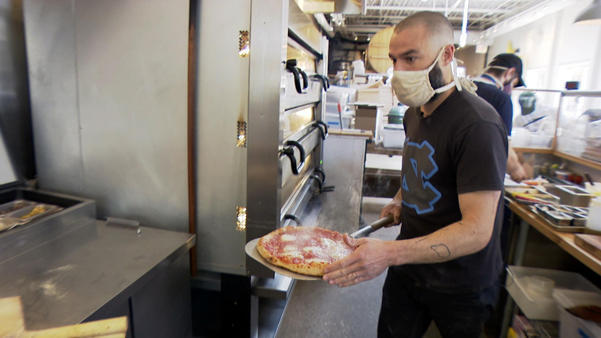 Pete Ternes, owner of the brewpub Bungalow by Middle Brow, takes a pizza out of the Logan Square restaurant's oven on April 30, 2021. Bungalow by Middle Brow is one of several vendors participating in this year's Logan Square Farmers Market. (WTTW News)