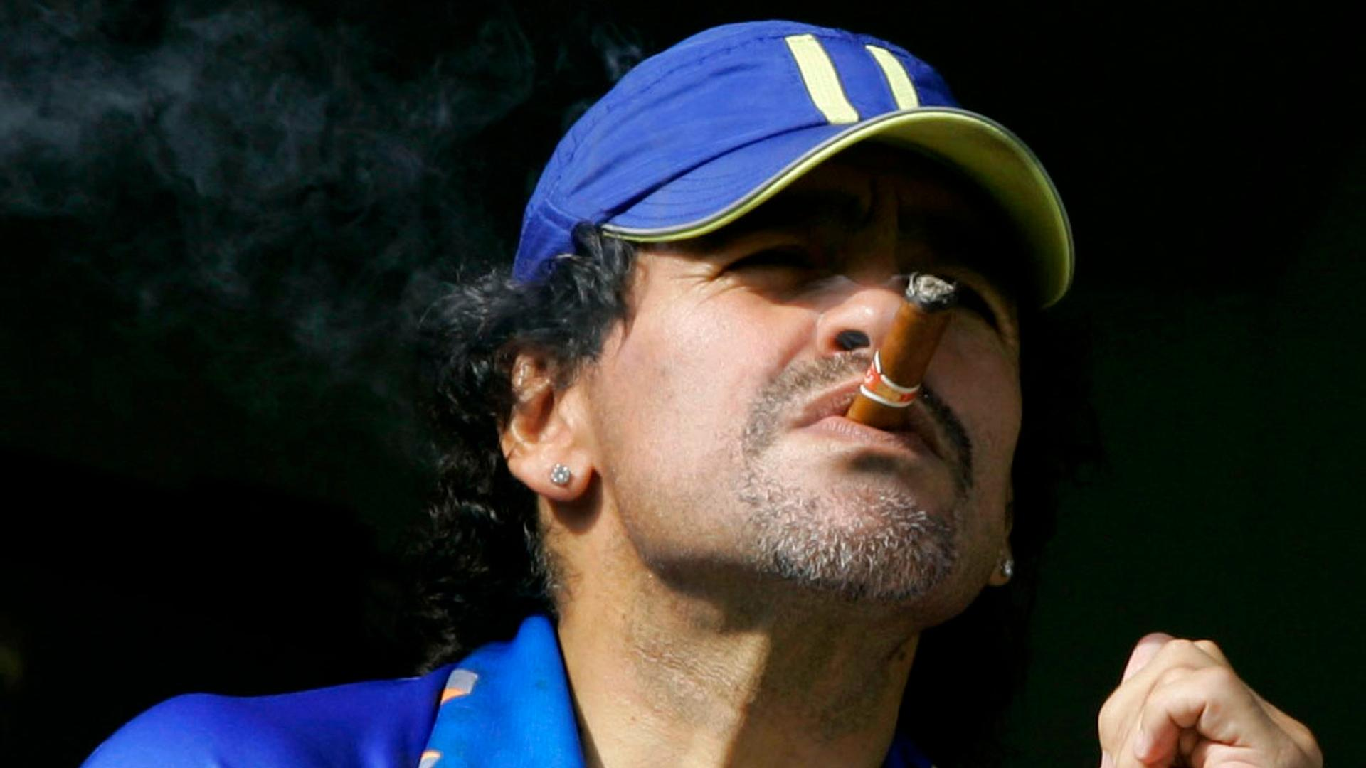 In this March 26, 2006 file photo, former soccer player Diego Maradona smokes a cigar as he watches Argentina's first division soccer match between Boca Juniors and River Plate in Buenos Aires, Argentina. (AP Photo / Natacha Pisarenko, File)