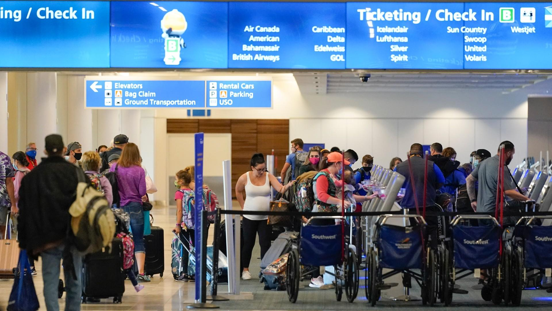 Holiday travelers check in at kiosks near an airline counter at Orlando International Airport Tuesday, Nov. 24, 2020, in Orlando, Fla. (AP Photo / John Raoux)
