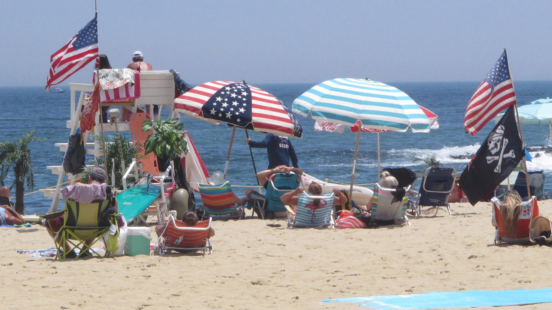 Flags line the beach in Belmar, N.J., on June 28, 2020. With large crowds expected at the Jersey Shore for the July Fourth weekend, some are worried that a failure to heed mask-wearing and social distancing protocols could accelerate the spread of the coronavirus. (AP Photo / Wayne Parry)