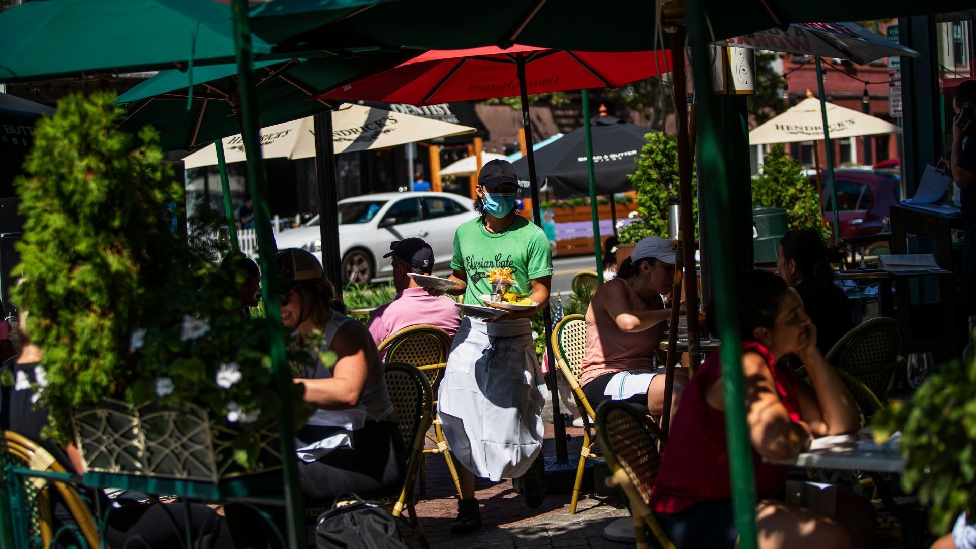 Un serveur portant un masque apporte de la nourriture à des tables devant un restaurant local pendant le déjeuner le vendredi 4 septembre 2020 à Hoboken, NJ (AP Photo / Eduardo Munoz Alvarez)