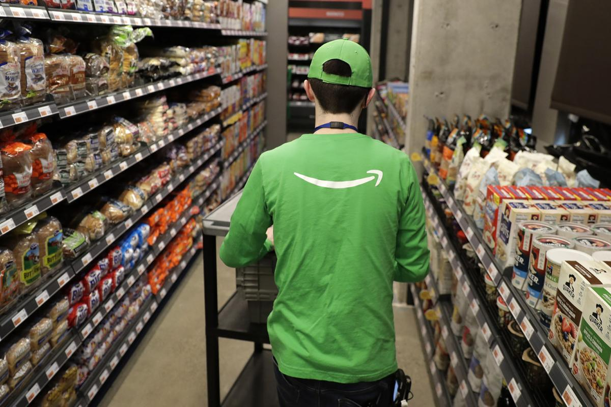 In this Feb. 21, 2020 photo, a worker pushes a cart inside an Amazon Go Grocery store set to open soon in Seattle's Capitol Hill neighborhood. (AP Photo / Ted S. Warren)
