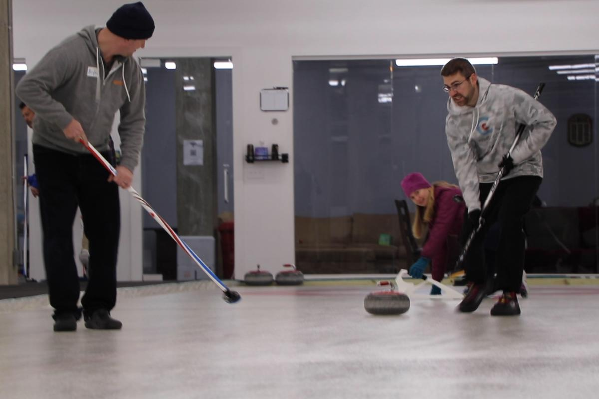 Sweepers follow a curling stone down a sheet of ice at the Windy City Curling Club in Villa Park, Illinois. (Evan Garcia / WTTW News)