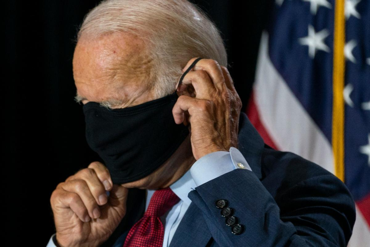 Democratic presidential candidate former Vice President Joe Biden joined by his running mate Sen. Kamala Harris, D-Calif., replaces his face mask after speaking at the Hotel DuPont in Wilmington, Del., Thursday, Aug. 13, 2020. (AP Photo / Carolyn Kaster)