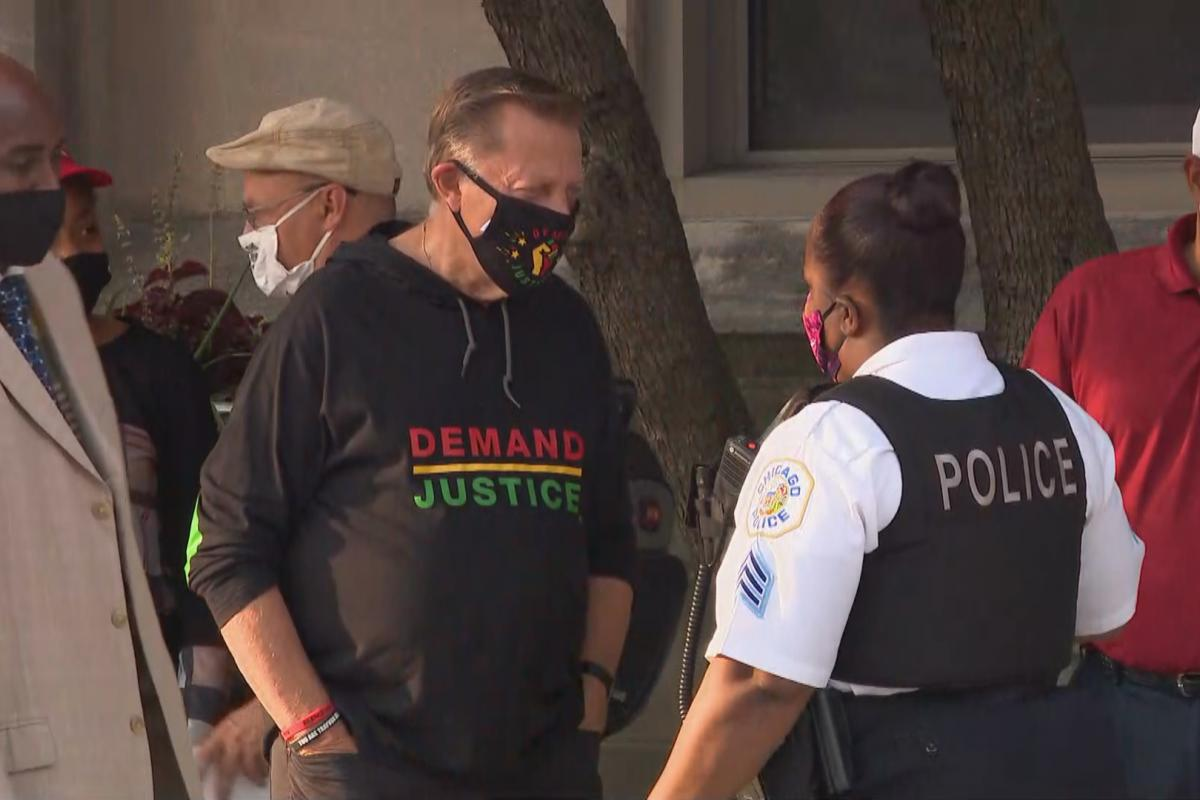 The Rev. Michael Pfleger speaks with a Chicago police officer outside St. Sabina Church during a protest over the grand jury decision in the Breonna Taylor case on Wednesday, Sept. 23, 2020. (WTTW News)