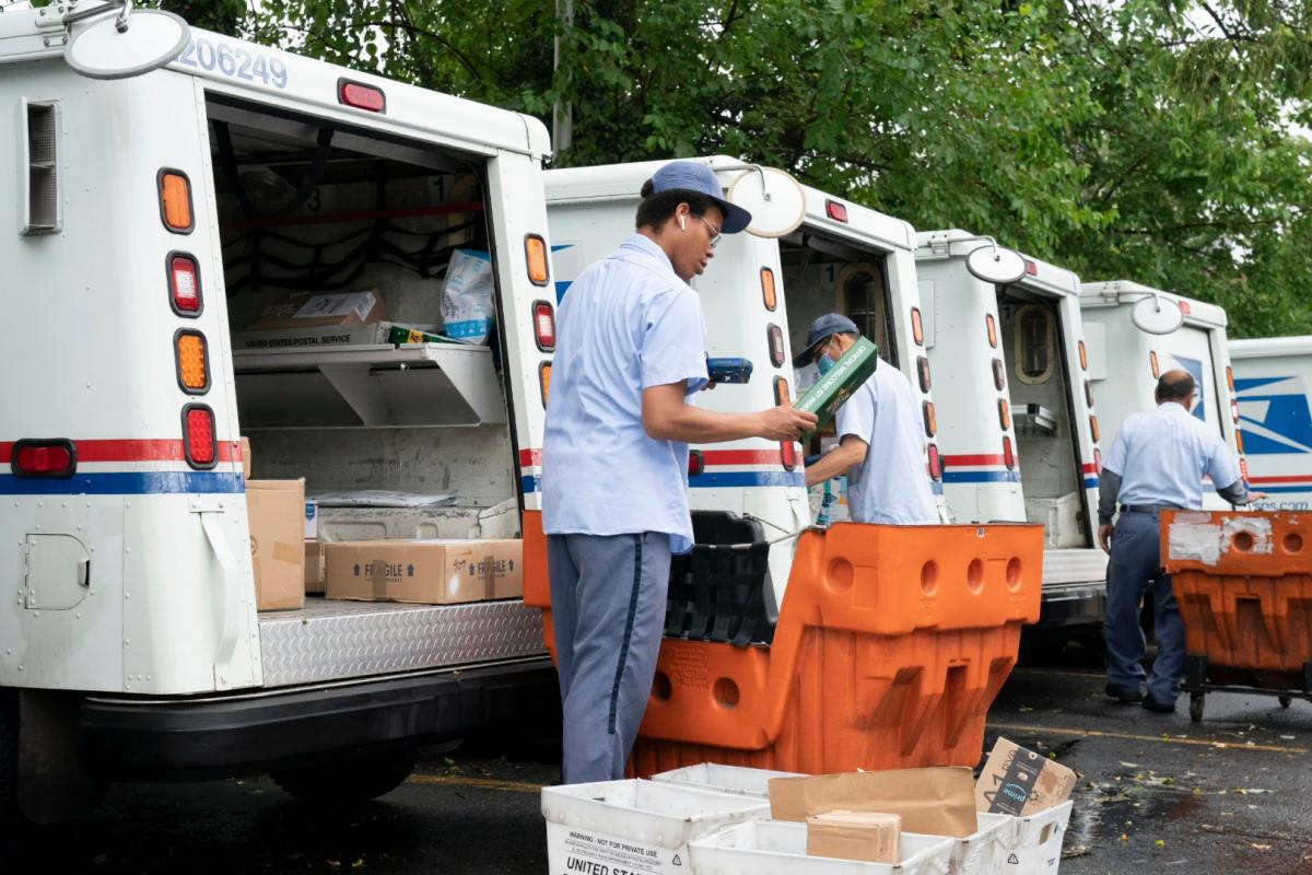 In this July 31, 2020, file photo, letter carriers load mail trucks for deliveries at a U.S. Postal Service facility in McLean, Va. (AP Photo / J. Scott Applewhite, File)