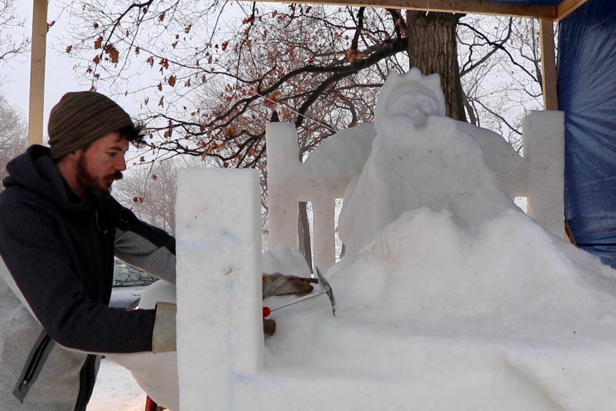 """Snow sculptor George Burnette works on his sculpture """"Don't Look Under the Bed"""" on Friday during the Illinois Snow Sculpting Competition in Rockford, Illinois. (Evan Garcia / WTTW)"""